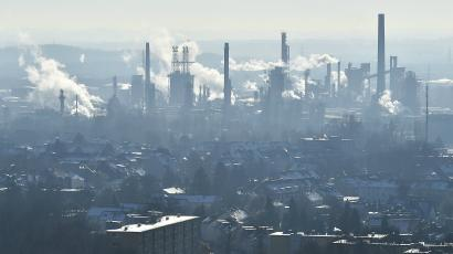 A man watches a steaming BP refinery in the city of Gelsenkirchen, Germany.