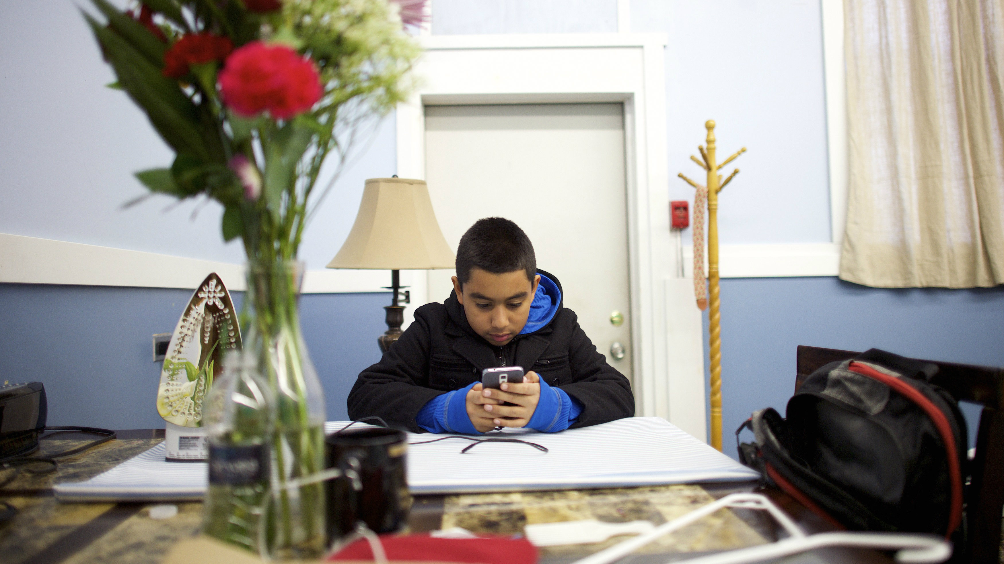 """Arturo, 11, the son of Angela Navarro, an undocumented Honduran-born immigrant with a deportation order, who moved into West Kensington Ministry Church with her family - her husband and two U.S. born children, uses his cell phone in Philadelphia, Pennsylvania November 18, 2014. Navarro, who has """"always lived in fear"""" of deportation said on Tuesday she moved into a Philadelphia church as part of a national civil disobedience action aimed at pressing President Obama on immigration reform. Navarro is the ninth undocumented immigrant who has taken refuge in a church recently as part of what activists are calling the New Sanctuary Movement. Organizers offer sanctuary in churches because federal guidelines prohibit arrests in sensitive areas unless there is a threat to public safety or national security. REUTERS/Mark Makela (UNITED STATES - Tags: SOCIETY IMMIGRATION POLITICS RELIGION)"""