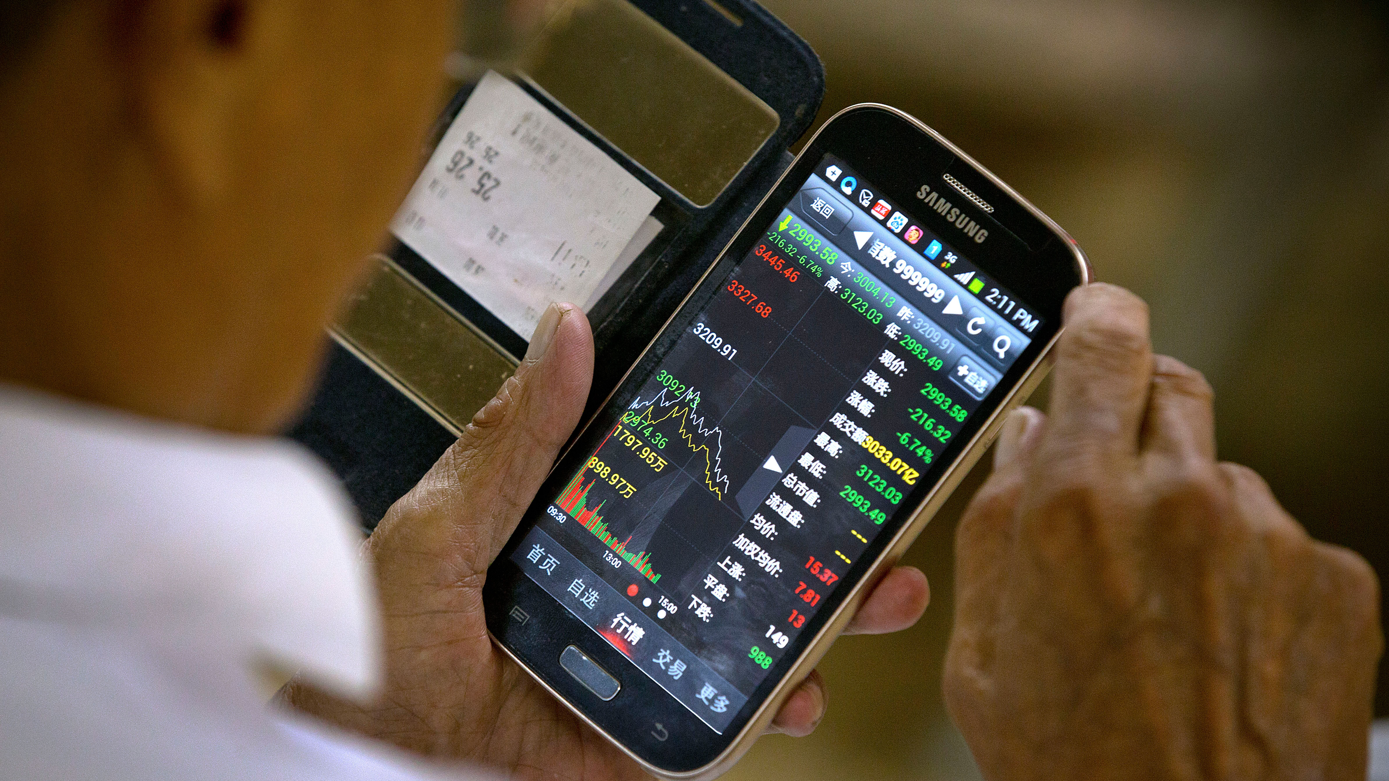 A Chinese investor uses his smartphone to monitor stock prices at a brokerage house in Beijing, Tuesday, Aug. 25, 2015. China's main stock market index has fallen for a fourth day, plunging 7.6 percent to an eight-month low. (AP Photo/Mark Schiefelbein)