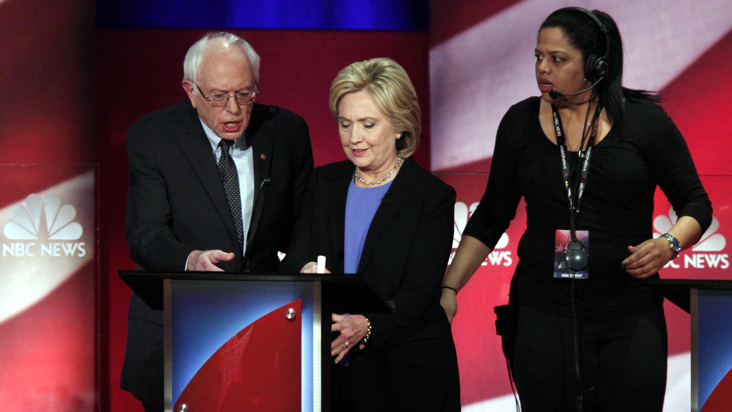 Democratic U.S. presidential candidate and U.S. Senator Bernie Sanders (L) assists rival candidate and former Secretary of State Hillary Clinton (C) with something at her podium as a network staff member (R) looks on during a break at the NBC News - YouTube Democratic presidential candidates debate in Charleston, South Carolina January 17, 2016.
