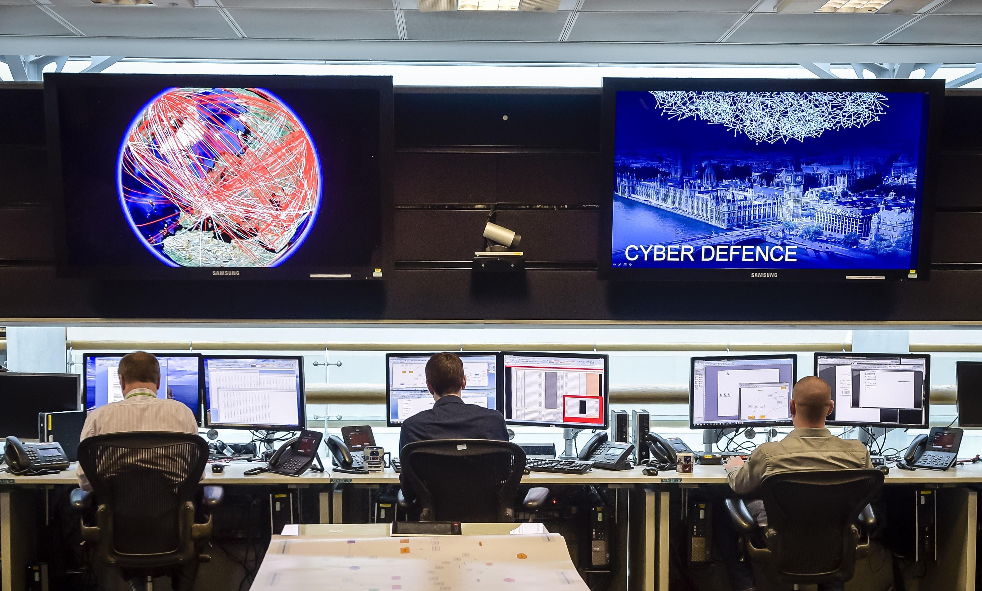 People at UK spy agency GCHQ looking at huge screens.