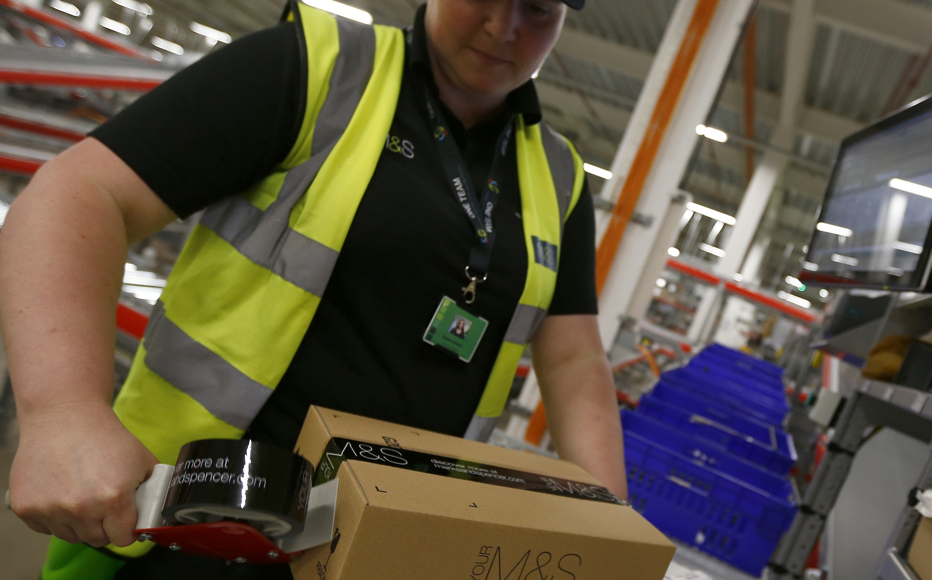 A worker boxes goods at the new Marks & Spencer e-commerce distribution centre in Castle Donington, central England May 8, 2013. The company was updating on its supply chain and IT investment programme, on Wednesday, to the media and to investors.   REUTERS/Darren Staples   (BRITAIN - Tags: BUSINESS) - RTXZF82