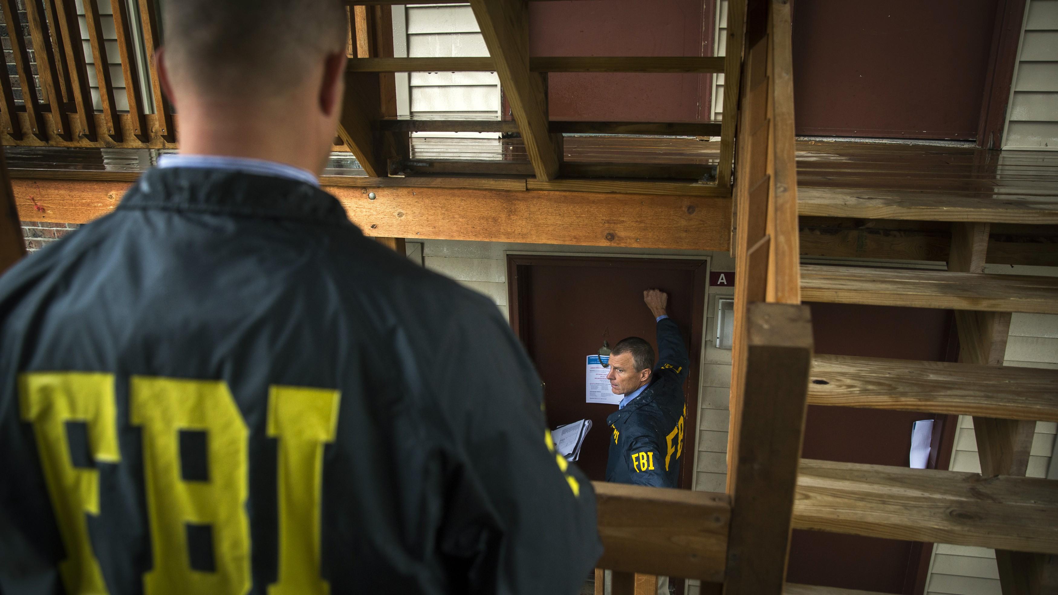 FBI agents knock on a door.