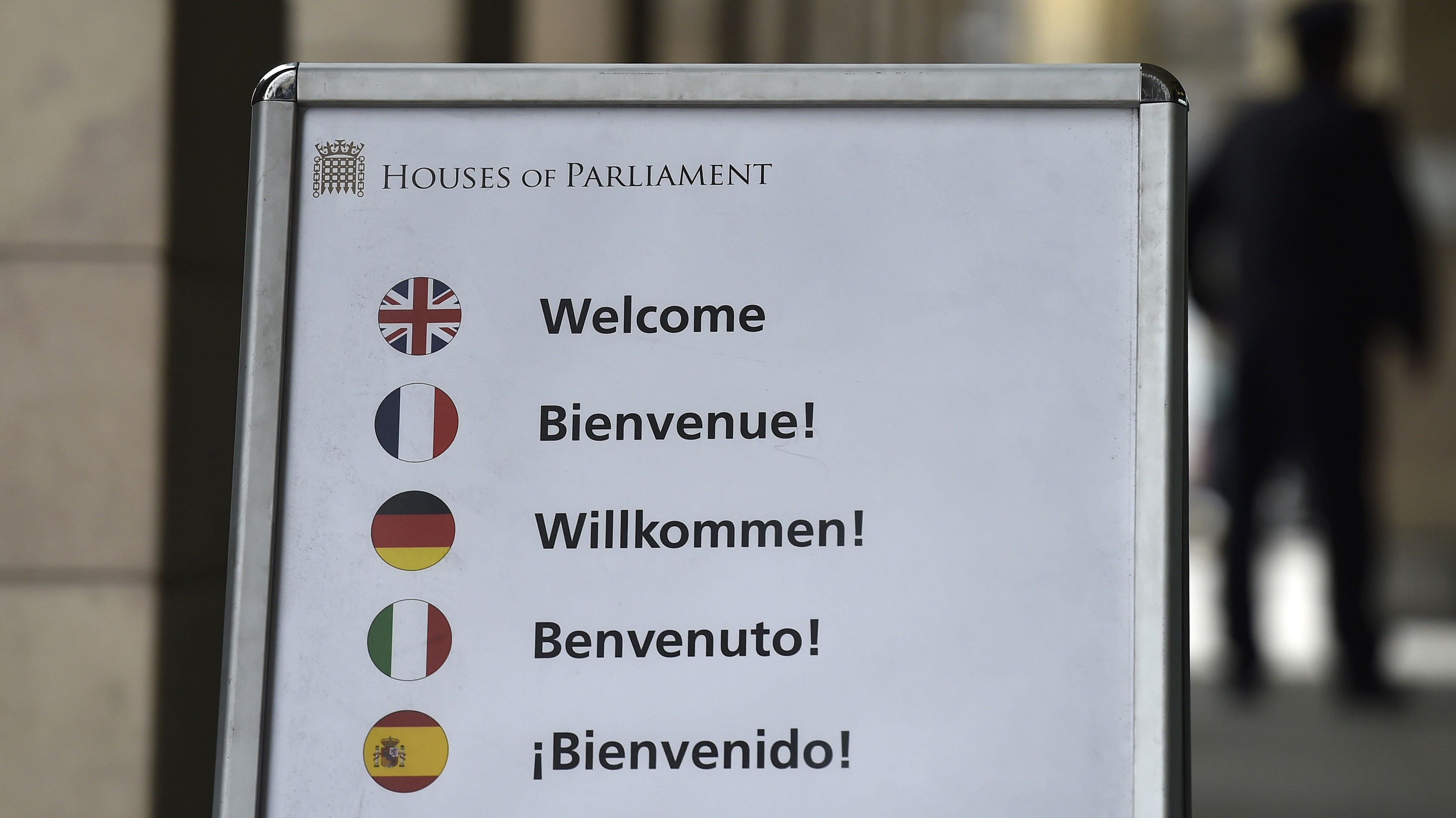 A board with various European language 'welcome' signage and national flag displays is seen outside of The Houses of Parliament in central London, Britain