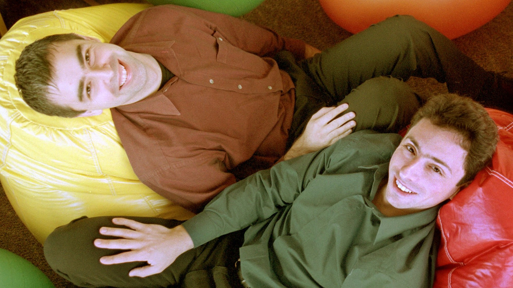 Google's co-founders, CEO Larry Page, left, and Chairman Sergey Brin, rest on bean bags at Google's headquarters on Friday, Nov. 11, 2000, in Mountain View, Calif. Google which replaced Inktomi as Yahoo's search engine in June is one of the few search engines that shuns pay-for-position and pay-for-inclusion. Google executives say those formulas make it more difficult for people to find potentially valuable information, like cancer research, on the Web. ``We have taken a very strong stance that our search results represent our editorial integrity,'' said Google CEO Larry Page.(AP Photo/Randi Lynn Beach)