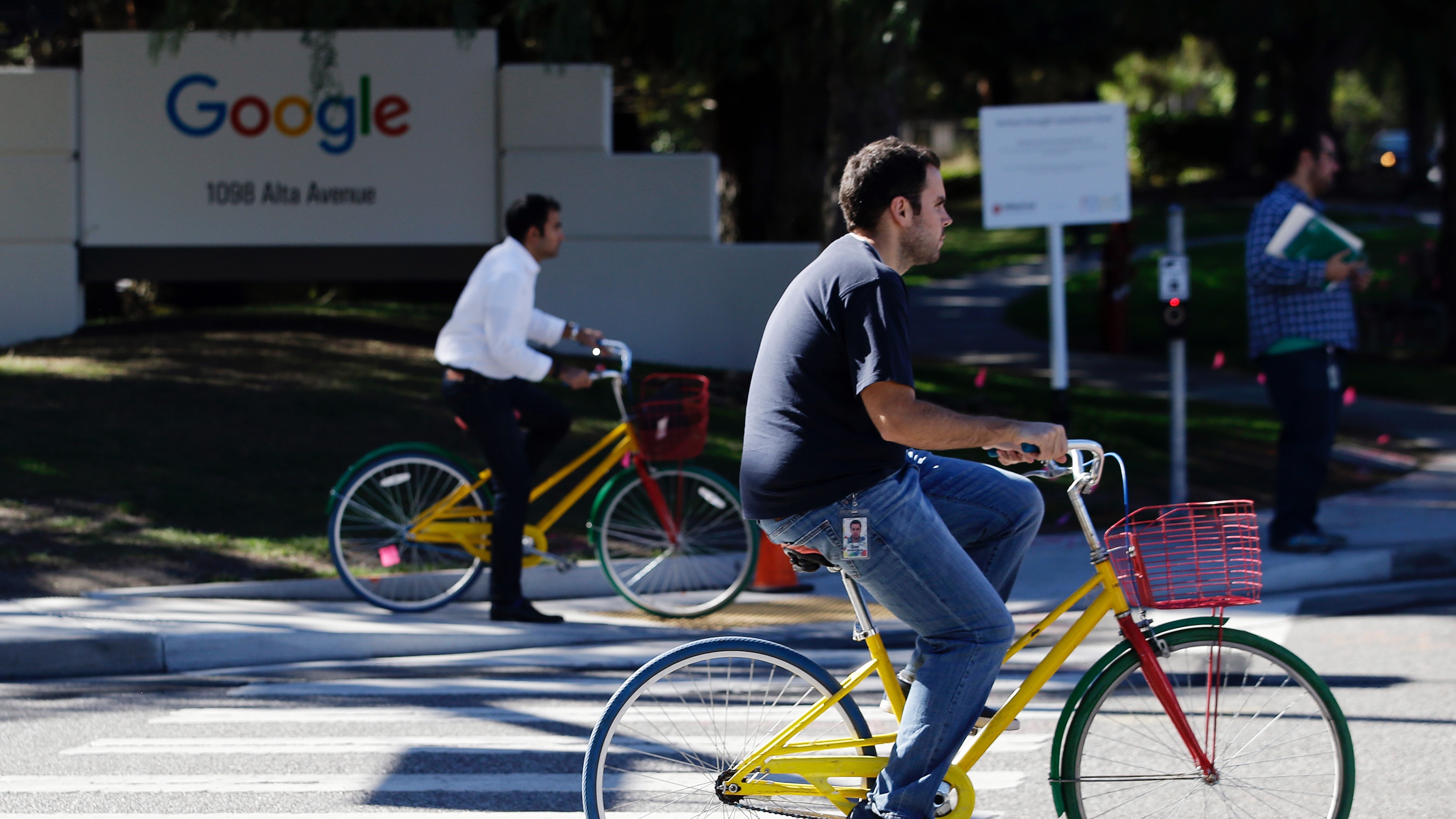 In this Oct. 20, 2015 photo, employees ride company bicycles outside Google headquarters in Mountain View, Calif. (AP Photo/Marcio Jose Sanchez)