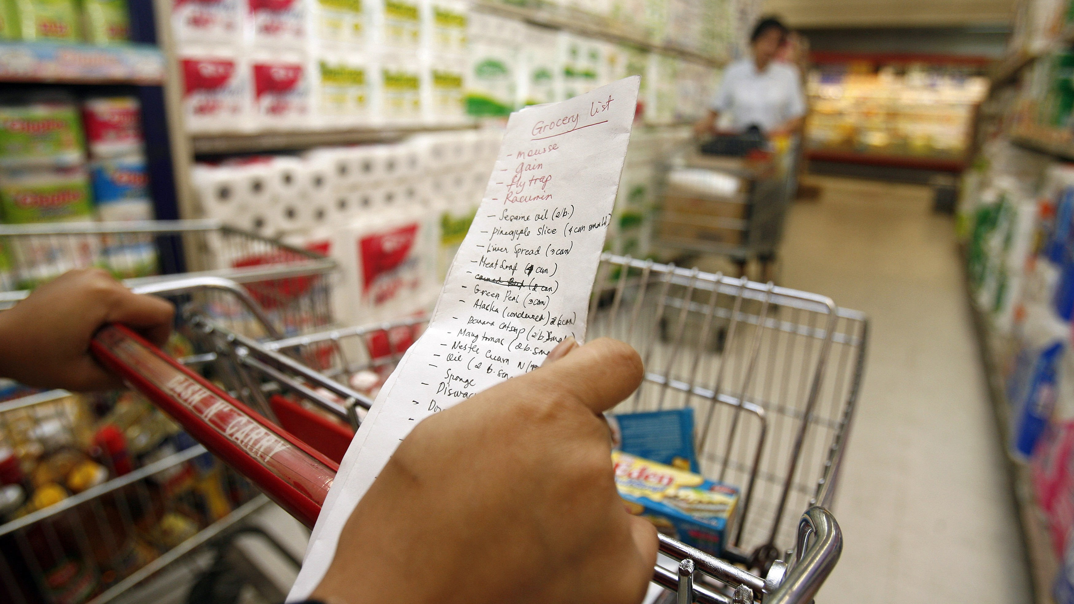A customer holds a grocery list as she shops at a supermarket in Manila's Makati financial district October 16, 2008. REUTERS/Cheryl Ravelo (PHILIPPINES) - RTX9RJU