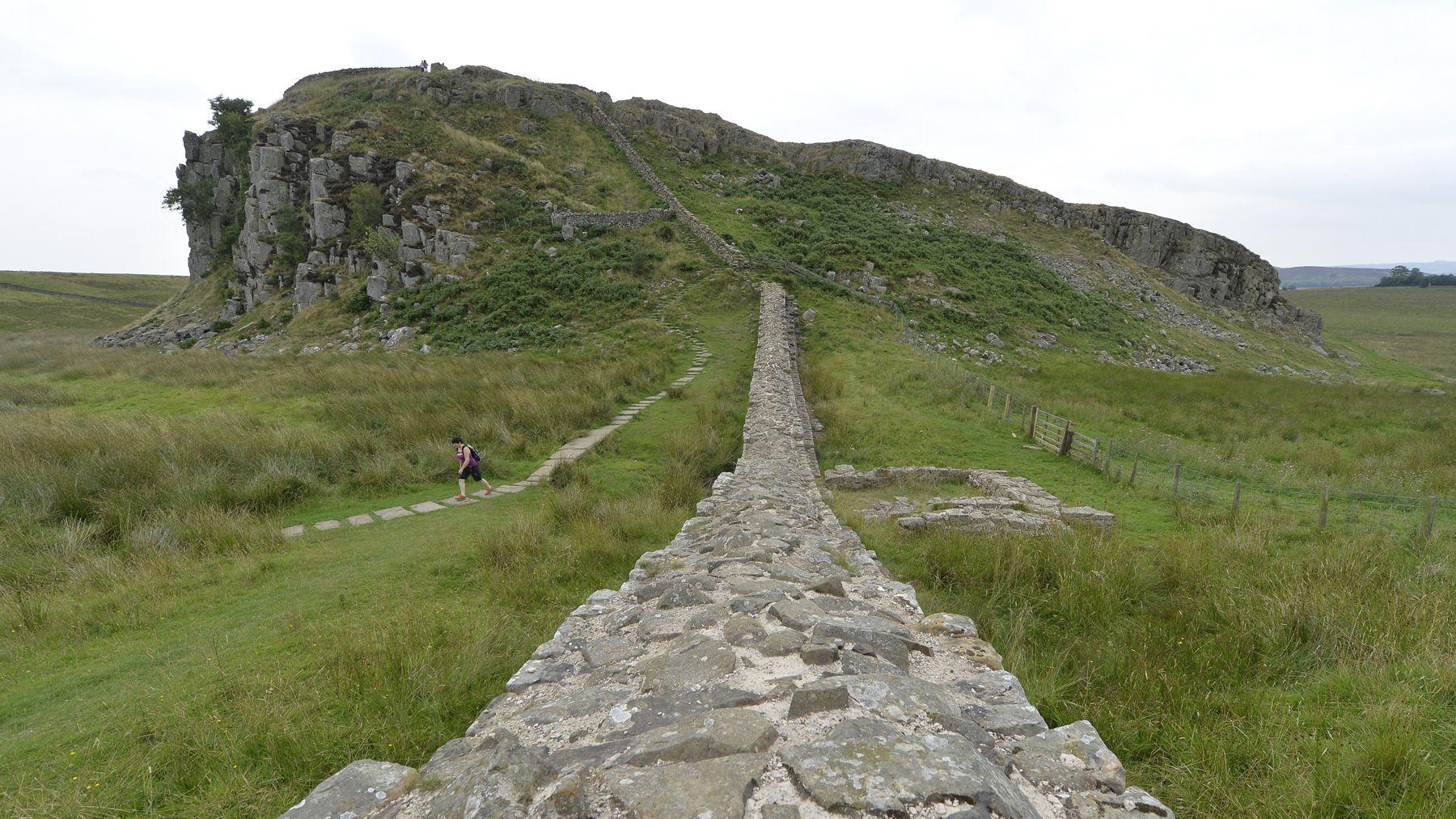 A rambler walks away from Peel Crag along Hadrian's Wall near Hexham in Northumberland August 23, 2013.