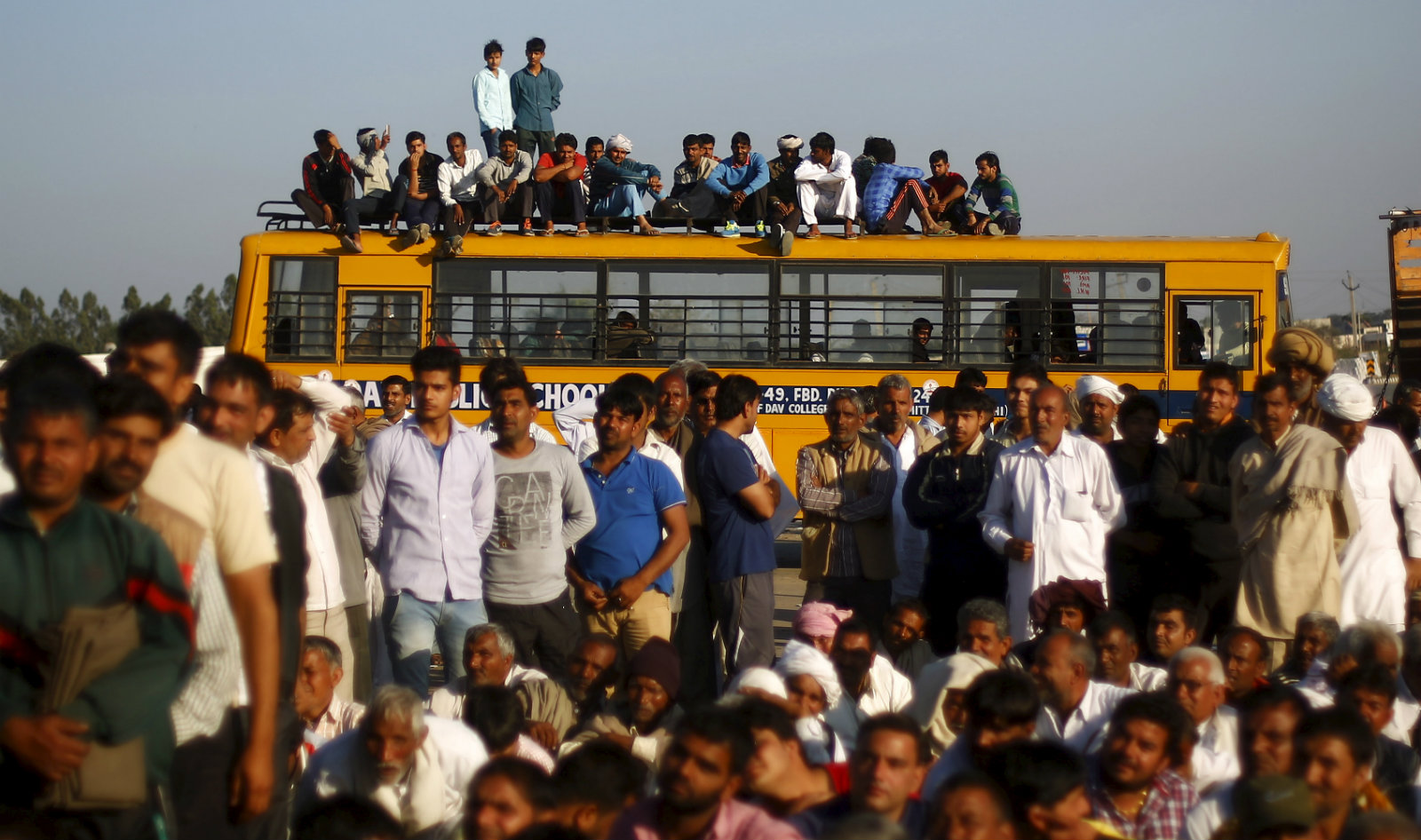 Demonstrators from the Jat community sit on top of a school bus as they block the Delhi-Haryana national highway during a protest at Sampla village in Haryana, India, February 21, 2016. India deployed thousands of troops in a northern state on Sunday to quell protests that have severely hit water supplies to Delhi, a metropolis of more than 20 million, forced factories to close and killed 10 people.