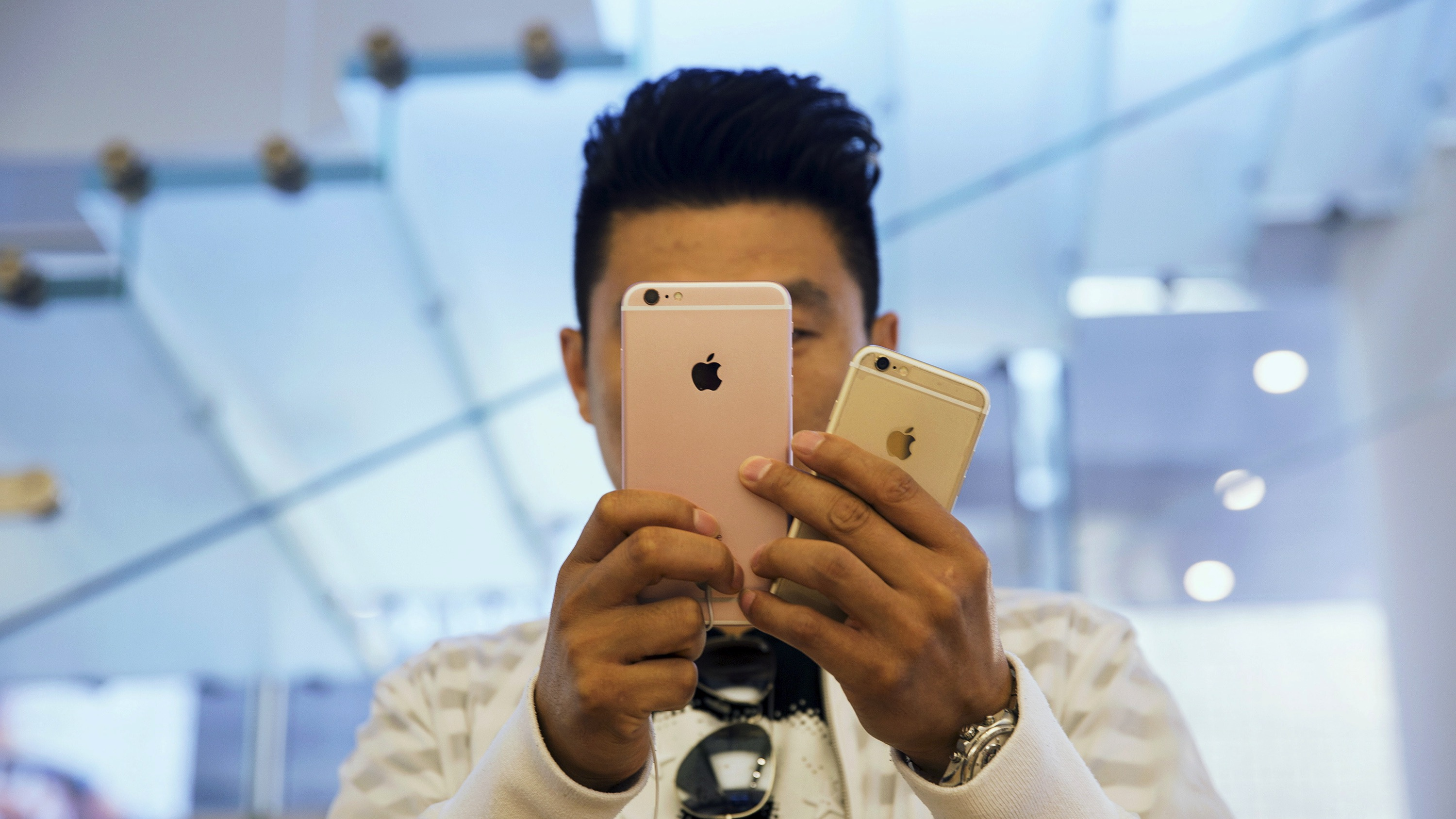 A man takes pictures as Apple iPhone 6s and 6s Plus go on sale at an Apple Store in Beijing, China September 25, 2015. The new iPhone 6s and 6s Plus arrived in stores and at consumers' doorsteps on Friday, kicking off a sales cycle that will be scrutinized for signs of how much juice Apple's marquee product has left.  REUTERS/Damir Sagolj - RTX1SCZI