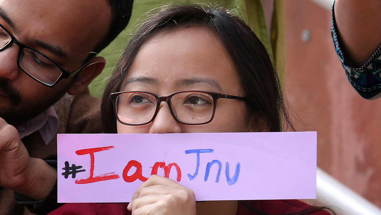 epa05164362 An Indian student of the Jawaharlal Nehru University (JNU) holds a placard during a protest inside JNU campus in New Delhi, India, 16 February 2016. A former Delhi University professor was arrested on 16 February for sedition, as protests escalated at another university whose students' union president was earlier detained for the same charge. Activists from the ruling Hindu nationalist Bharatiya Janata Party's student wing and right-wing organizations, which accuse demonstrators of being 'anti-nationals', also gathered near the university for counter-protests. EPA/RAJAT GUPTA