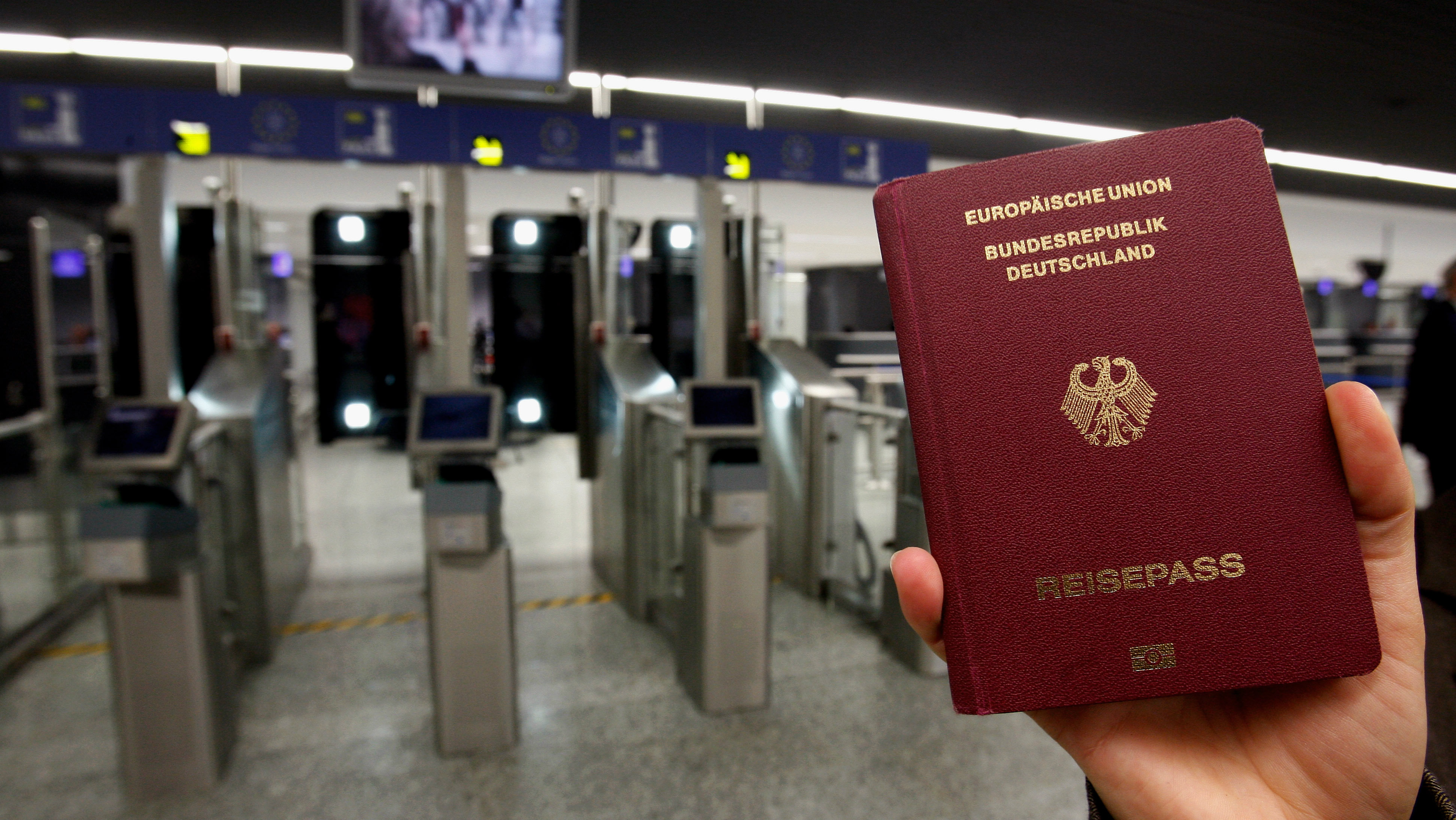 FRANKFURT AM MAIN, GERMANY - OCTOBER 16: A woman holds up passport during the presentation of the new automated border control system easyPass at Frankfurt International Airport on October 16, 2009 in Frankfurt am Main, Germany. EasyPass system automatically scans the biometric data of a passenger and compares it to the data in the passenger's e-passport, which has to be put into a document reader at the border control. (Photo by Alex Grimm/Getty Images)