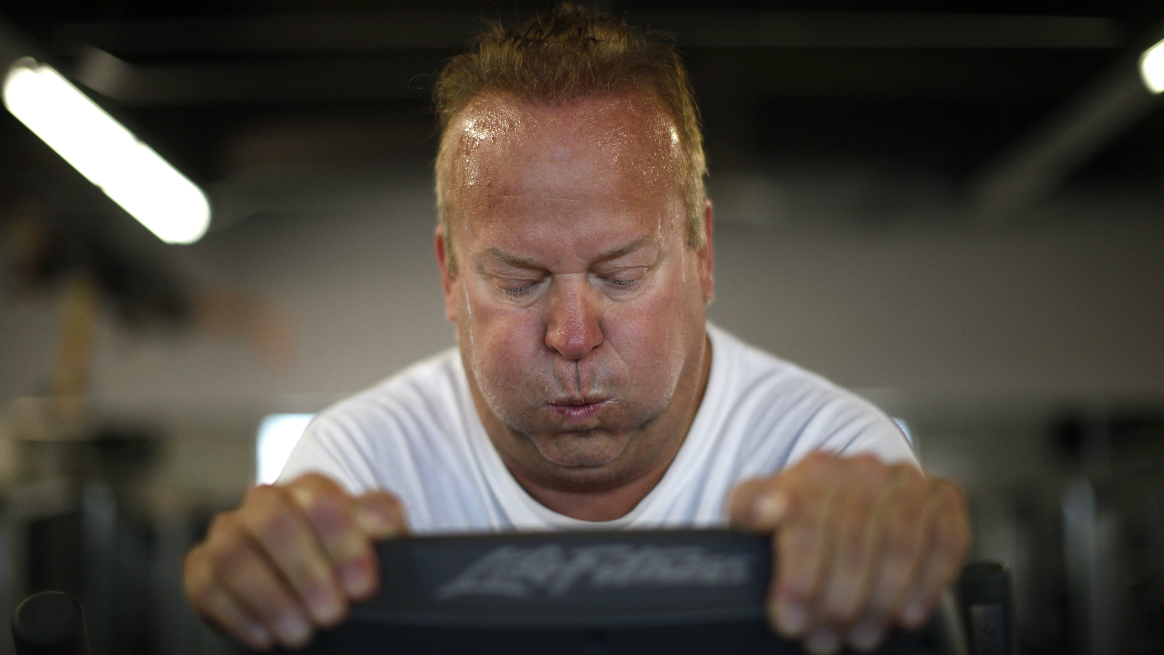 """Guests Richard Walker works out on an elliptical machine in the """"mountain"""" fitness class at the Biggest Loser Resort in Ivins, Utah September 6, 2010. Guests at the resort affiliated with the popular reality television show are restricted to a daily 1,200 calorie diet and exercise 6 to 7 hours a day. REUTERS/Rick Wilking"""