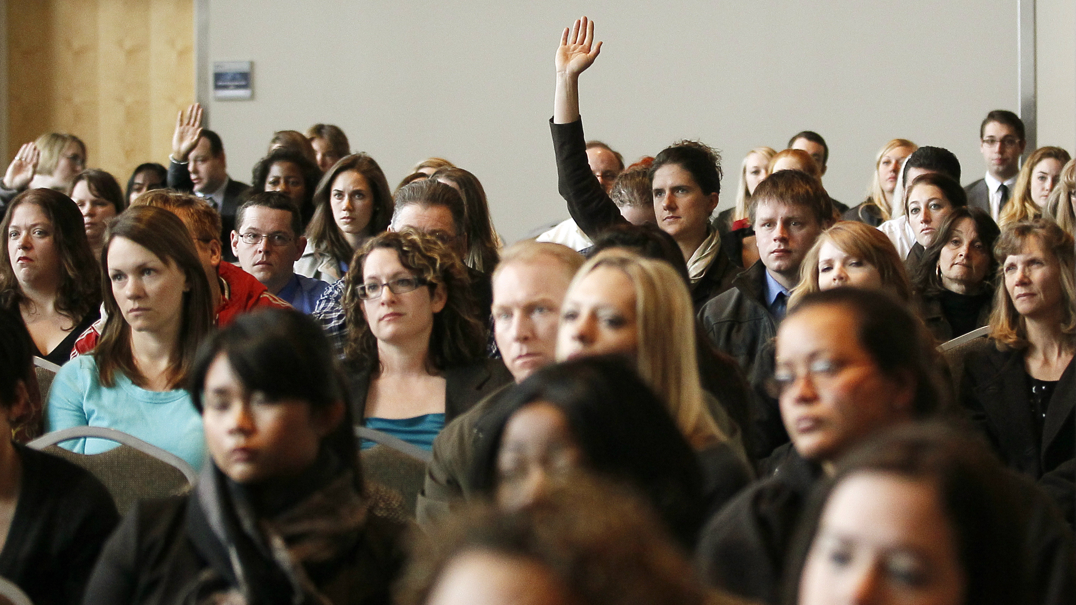 A job seeker raises his hand to ask a question at the Colorado Hospital Association health care career fair in Denver April 9, 2013. Over 700 registered for the event with over 30 health care providers represented. REUTERS/Rick Wilking (UNITED STATES - Tags: BUSINESS EMPLOYMENT HEALTH)