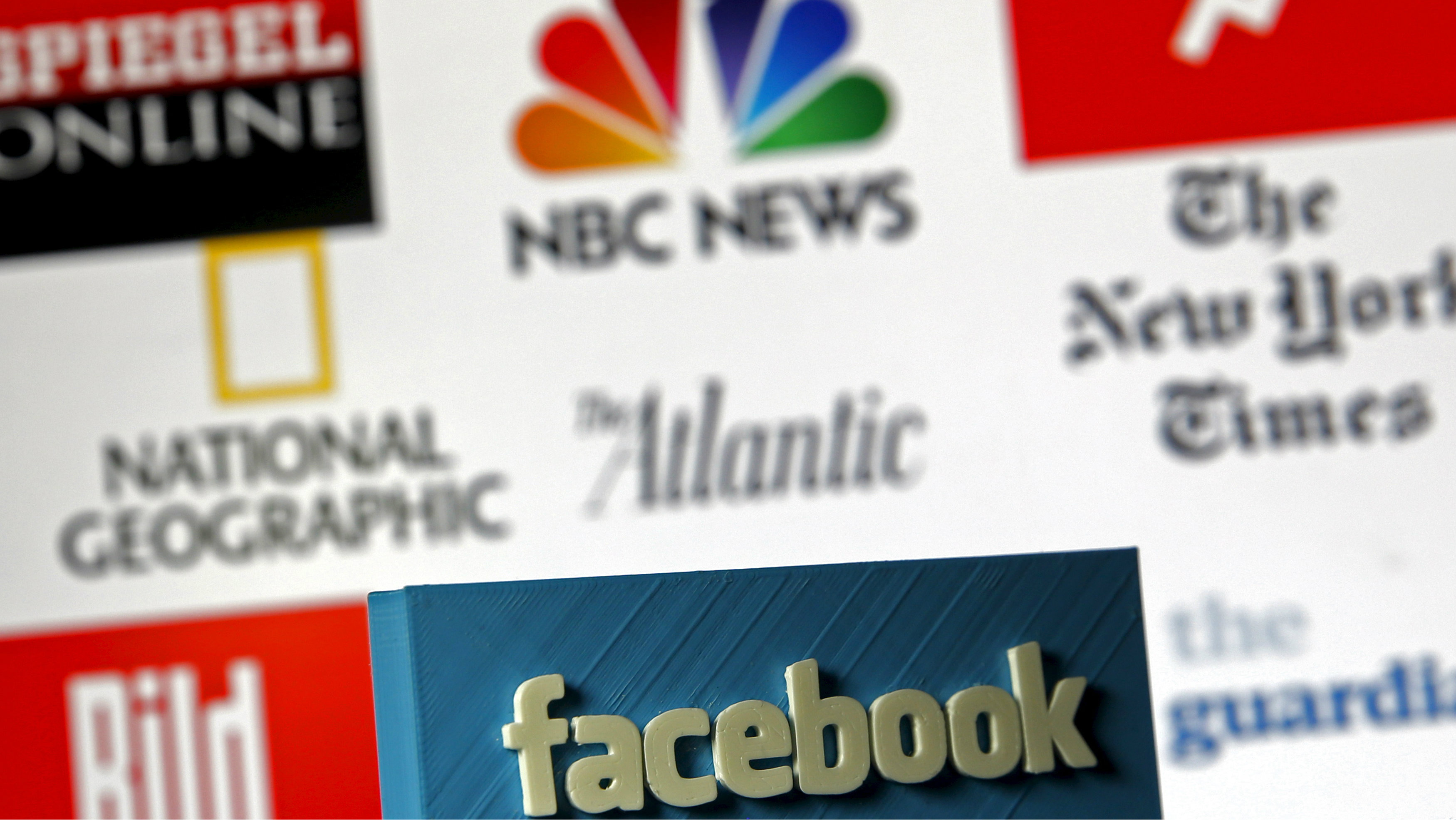 """A 3D-printed Facebook logo is seen in front of logos of news publishers it has tied up with, in this picture illustration made in Zenica, Bosnia and Herzegovina on May 15, 2015. Facebook Inc tied up with nine news publishers to launch """"Instant Articles"""" that will let them publish articles directly to the social network's mobile news feeds. Instant Articles will let stories load more than 10 times faster than standard mobile web articles and will include content from publishers such as the New York Times, BuzzFeed and National Geographic, Facebook said in a blog post on its website. The other launch partners for Instant Articles are NBC, The Atlantic, The Guardian, BBC News, Spiegel and Bild, Facebook said. REUTERS/Dado Ruvic"""