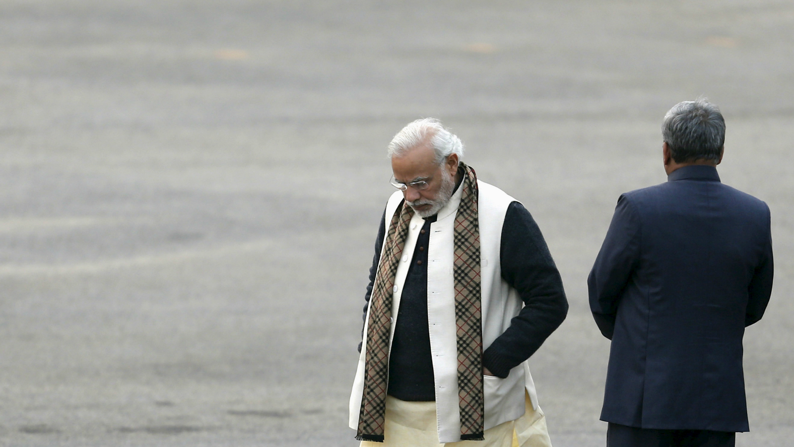 """India's Prime Minister Narendra Modi (L) and Defence Minister Manohar Parrikar wait for the arrival of President Pranab Mukherjee before the start of the """"Beating the Retreat"""" ceremony in New Delhi, India, January 29, 2016. The ceremony symbolises retreat after a day on the battlefield, and marks the official end of the Indian Republic Day celebrations."""