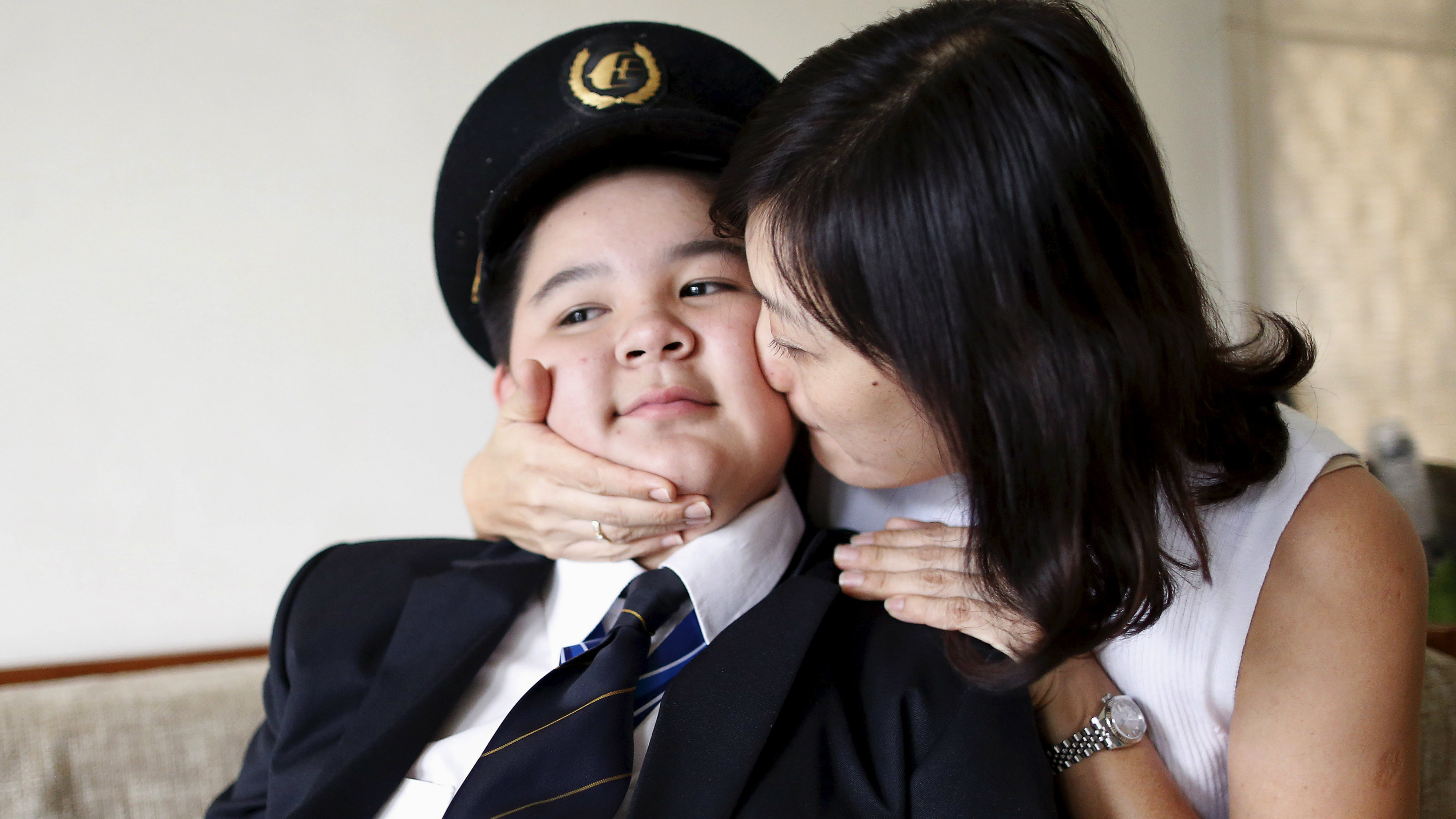 Ivy Loi, wife of MH17 co-pilot Eugene Choo, kisses her son Scott Choo, 12, as he poses for a photograph in his father's uniform at home in Seremban, near Kuala Lumpur, Malaysia, October 13, 2015. Malaysia Airlines Flight 17 was shot down over eastern Ukraine by a Russian-made Buk missile, the Dutch Safety Board concluded on Tuesday in its final report on the July 2014 crash that killed all 298 people on board. REUTERS/Olivia Harris