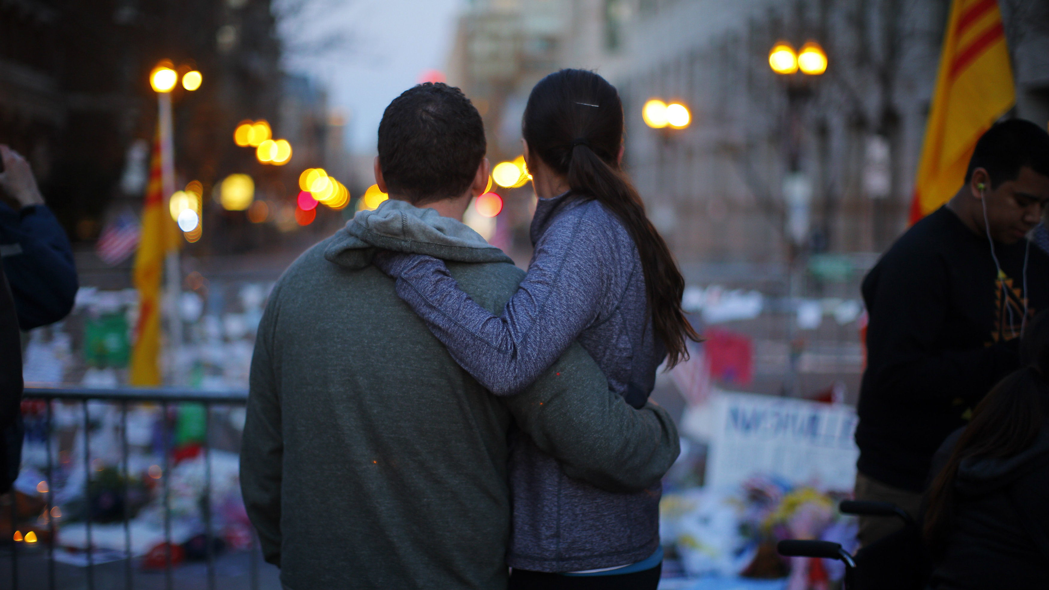 A couple embraces at a memorial on Boylston Street to the victims of the Boston Marathon bombings in Boston, Massachusetts April 21, 2013. Two explosions hit the Boston Marathon on April 15 killing at least three people and injuring over 100 others. REUTERS/Brian Snyder (UNITED STATES - Tags: CRIME LAW)