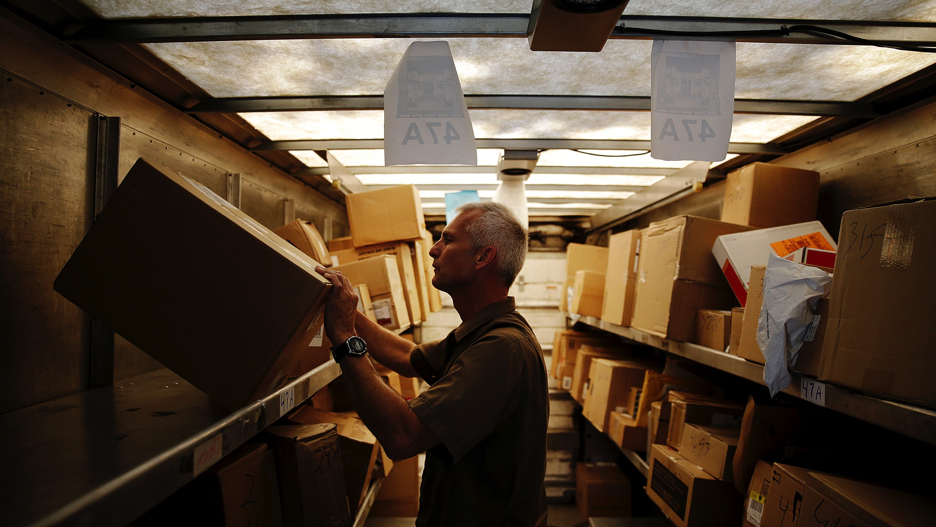 In this June 20, 2014 photo, United Parcel Service driver Marty Thompson checks the information on boxes in the back of his truck while making a delivery in Cumming, Ga. UPS on Wednesday, Oct. 29, 2014 said it expects to deliver more than 34 million packages on Monday, Dec. 22, the busiest day of the holiday season, double the amount on a normal day. Six days are expected to top last year's single-day record of 31 million packages. (AP Photo/David Goldman)