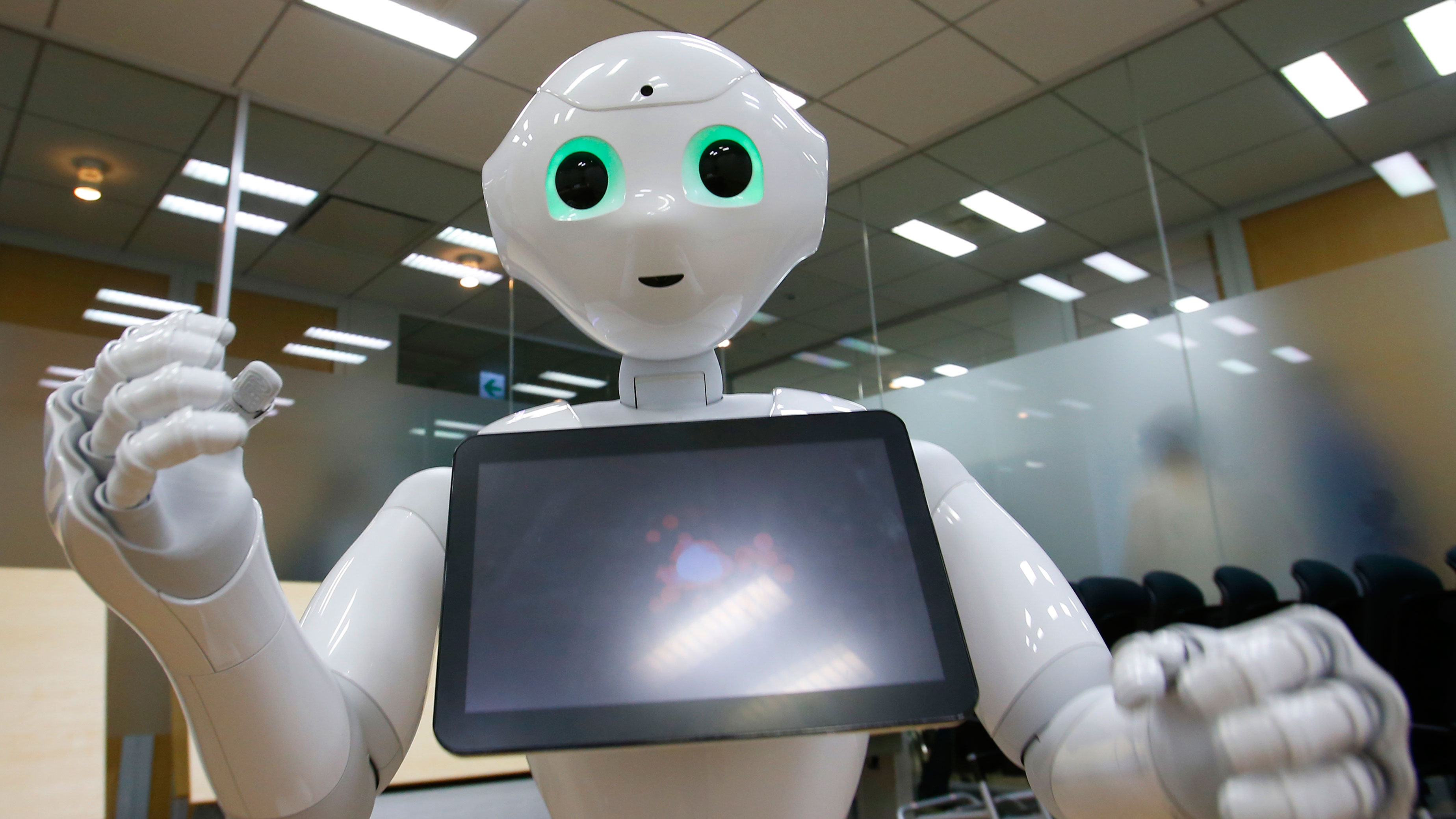 In this photo taken Thursday, July 9, 2015, SoftBank Corp.'s new companion robot Pepper performs during an interview at the technology company's headquarters in Tokyo. Pepper, the 121-centimeter (four-foot) tall white machine-on-wheels, offers ardent attention, cool dance moves, and small talk. Pepper has cameras, lasers and infrared in its hairless head so it can detect human faces. (AP Photo/Shizuo Kambayashi)