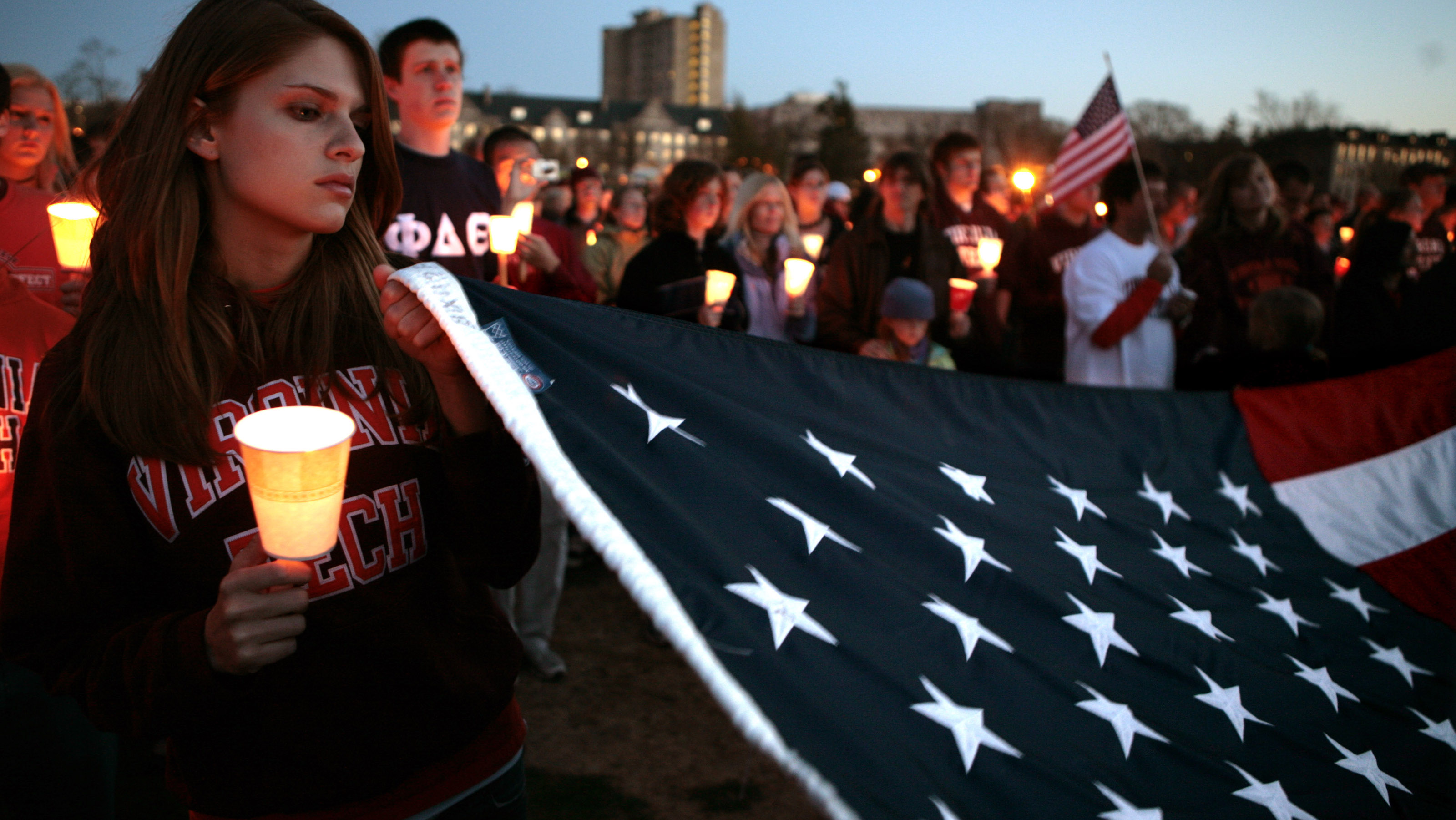 A student holds a corner of the American flag during a candlelight  vigil a day after the killings at Virginia Tech in  Blacksburg, Virginia, April 17, 2007.  Virginia Tech senior Cho Seung-Hui killed 32 people on Monday at Virginia Tech University after opening fire on students and staff in an apparently premeditated massacre on Monday morning, leaving the sprawling rural campus reeling with grief and shock.   REUTERS/Kevin Lamarque  (UNITED STATES) - RTR1OQW2