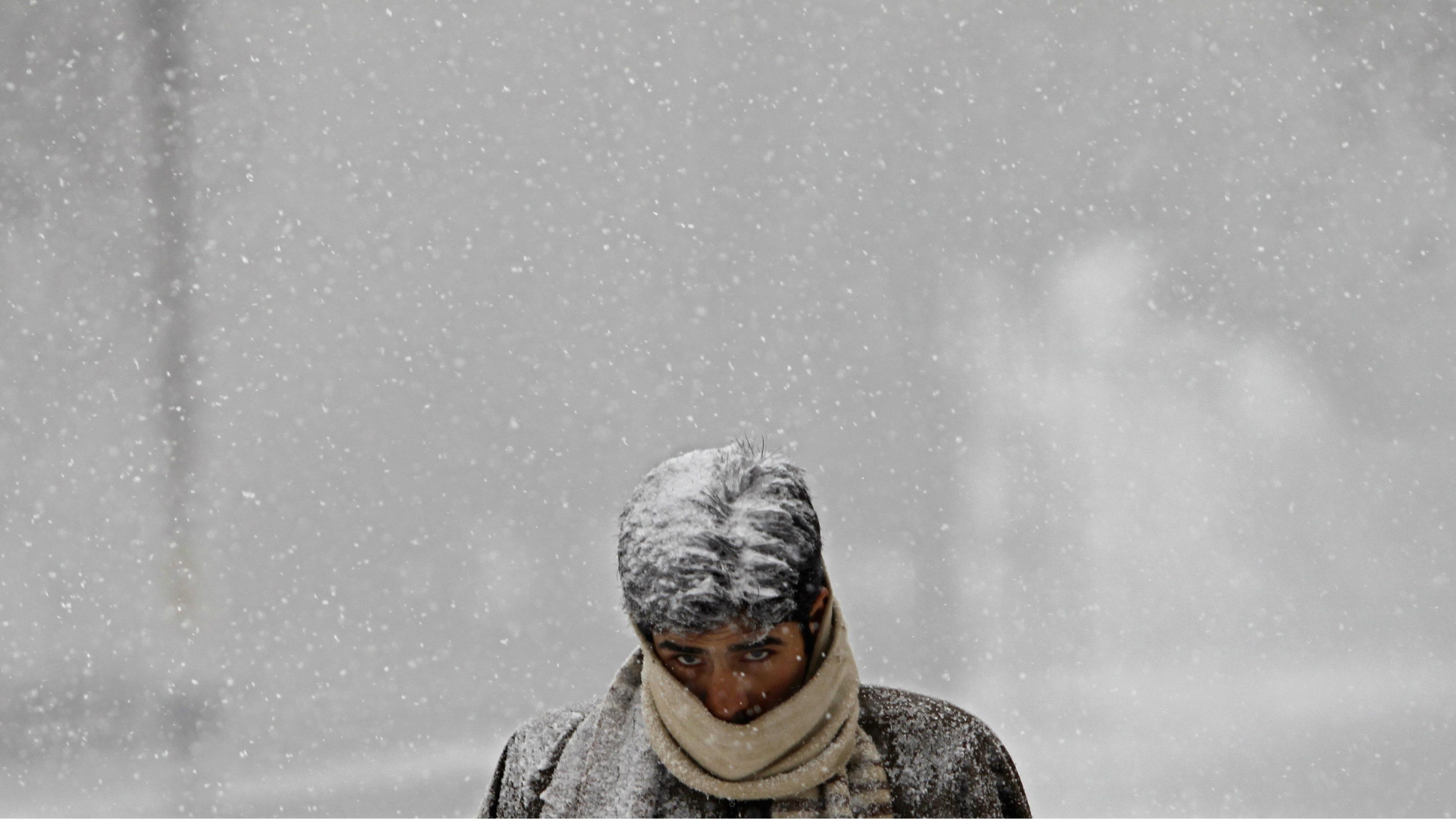 A Kashmiri man walks along a road during a snowfall in Srinagar.