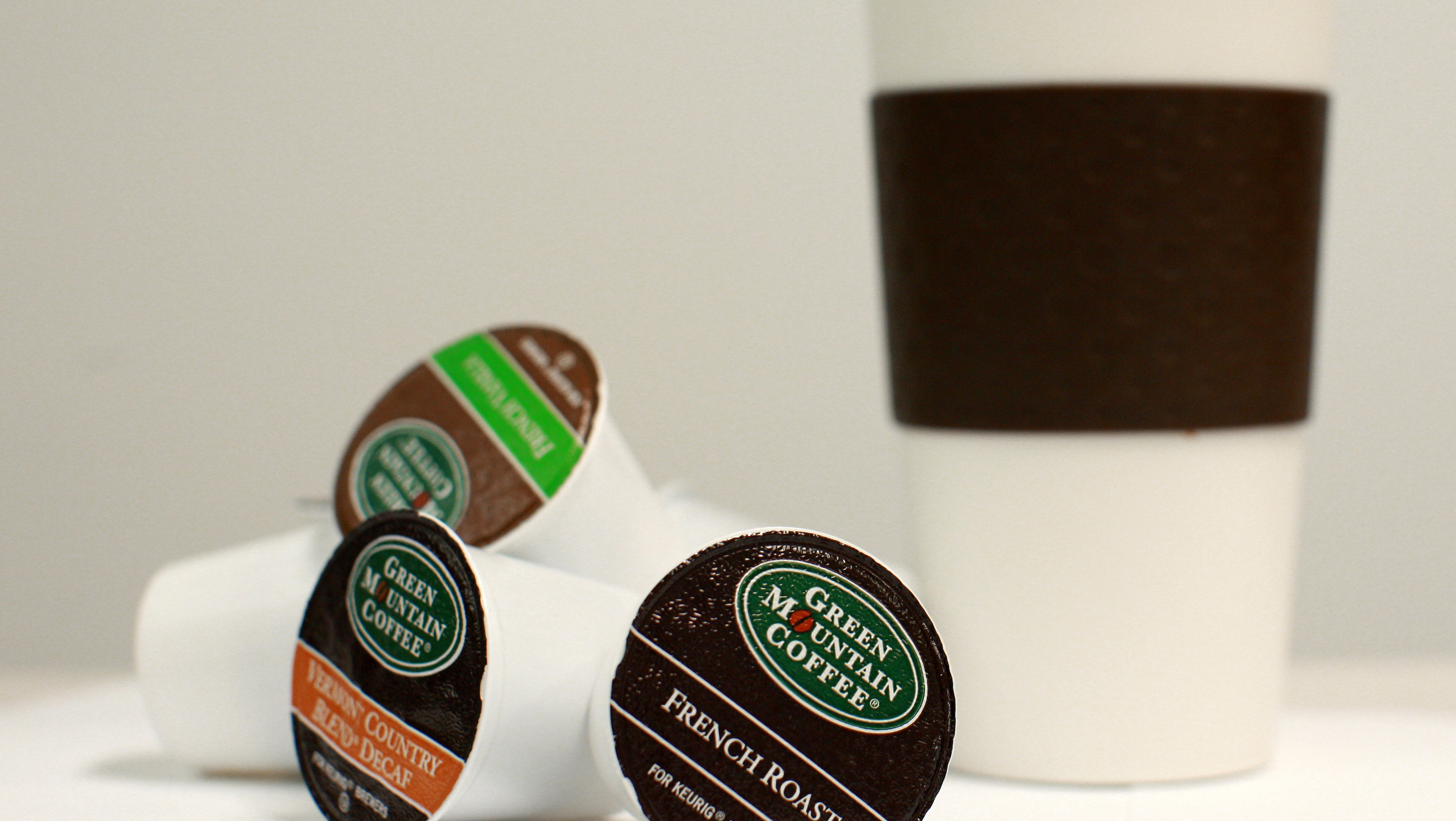 Green Mountain Coffee single-serve K-Cups are pictured with a coffee cup in New York, May 3, 2012. The company's management is quickly losing credibility with Wall Street after it badly missed sales estimates for the second time in three quarters, wiping out close to half of its market value. REUTERS/Brendan McDermid (UNITED STATES - Tags: FOOD BUSINESS) - RTR31KKD