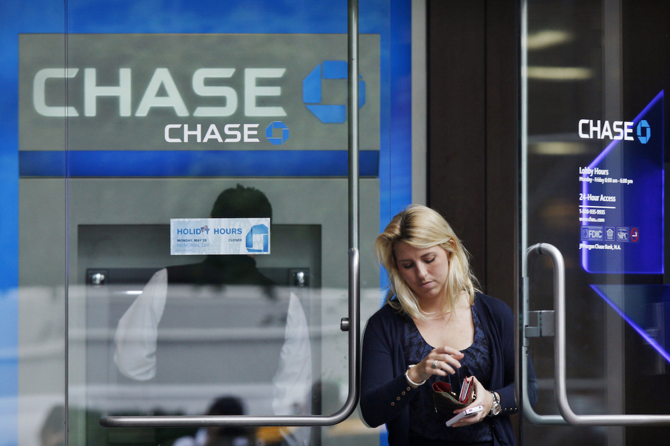 A customer exits the lobby of JPMorgan Chase & Co. headquarters in New York May 22, 2012.  JPMorgan Chase & Co has been hit with a lawsuit brought on behalf of employees whose retirement holdings fell in value after the largest U.S. bank revealed a surprise $2 billion trading loss earlier this month.