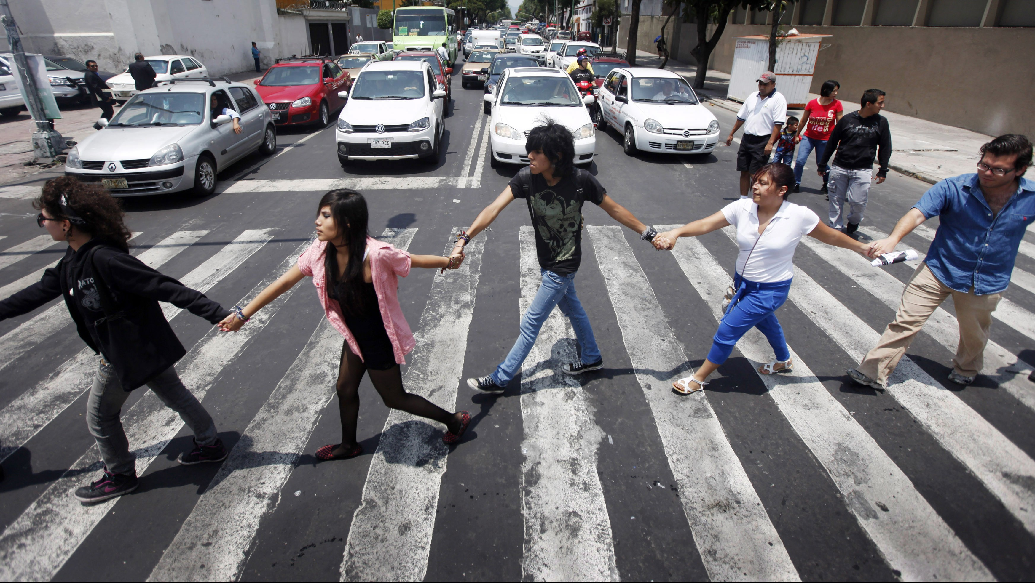 "Members of the movement ""Yosoy132"" (I am 132) walk hand in hand on a street during a demonstration to demand transparency in the next election in Mexico city"
