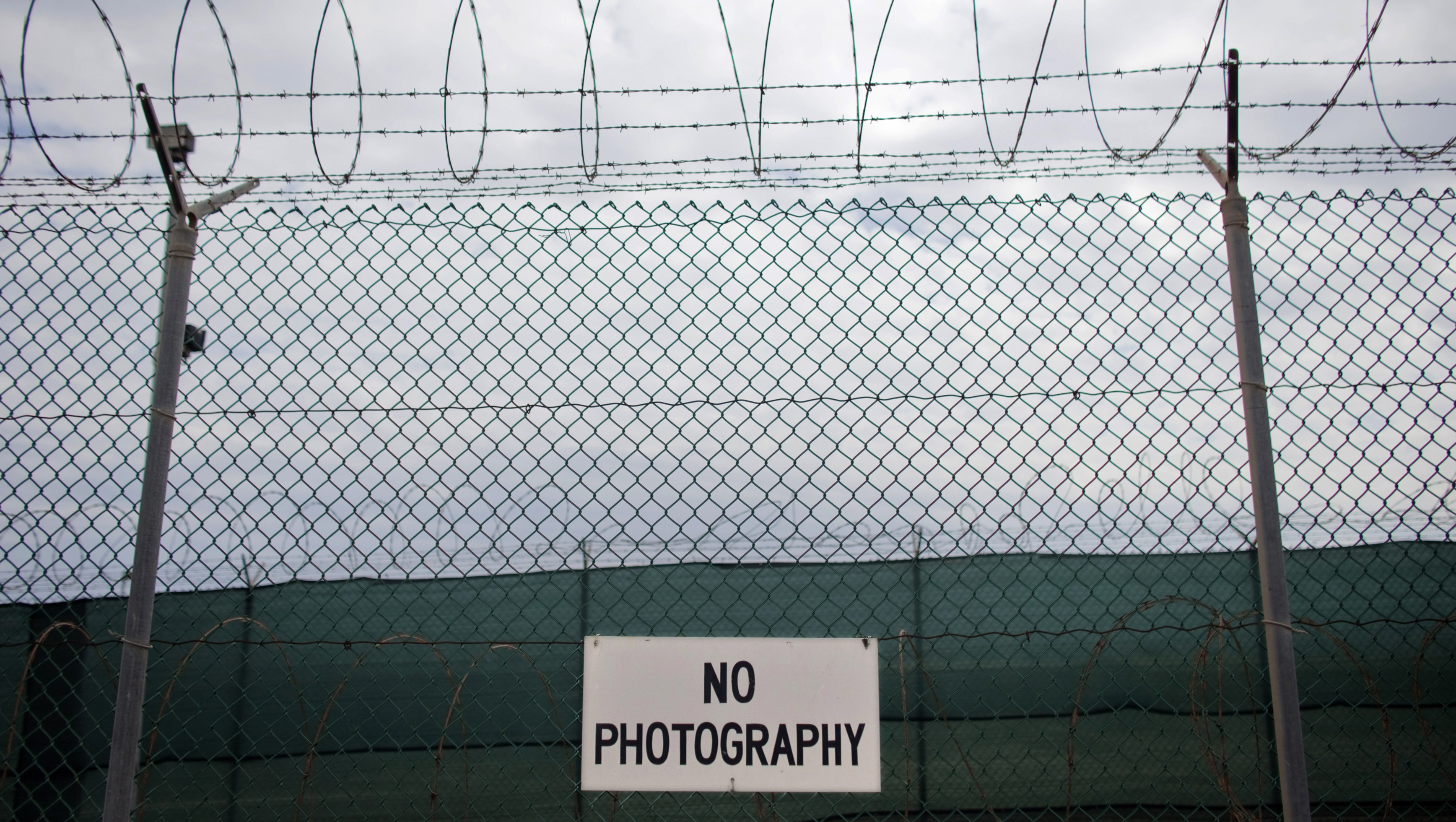 No photography signs are posted on the fence surrounding Camp Delta at the U.S. Naval Base at Guantanamo Bay, March 6, 2013. The facility is operated by the Joint Task Force Guantanamo and holds prisoners who have been captured in the war in Afghanistan and elsewhere since the September 11, 2001 attacks. Picture taken March 6, 2013. REUTERS/Bob Strong  (CUBA - Tags: POLITICS MILITARY CRIME LAW) - RTR3ETZL