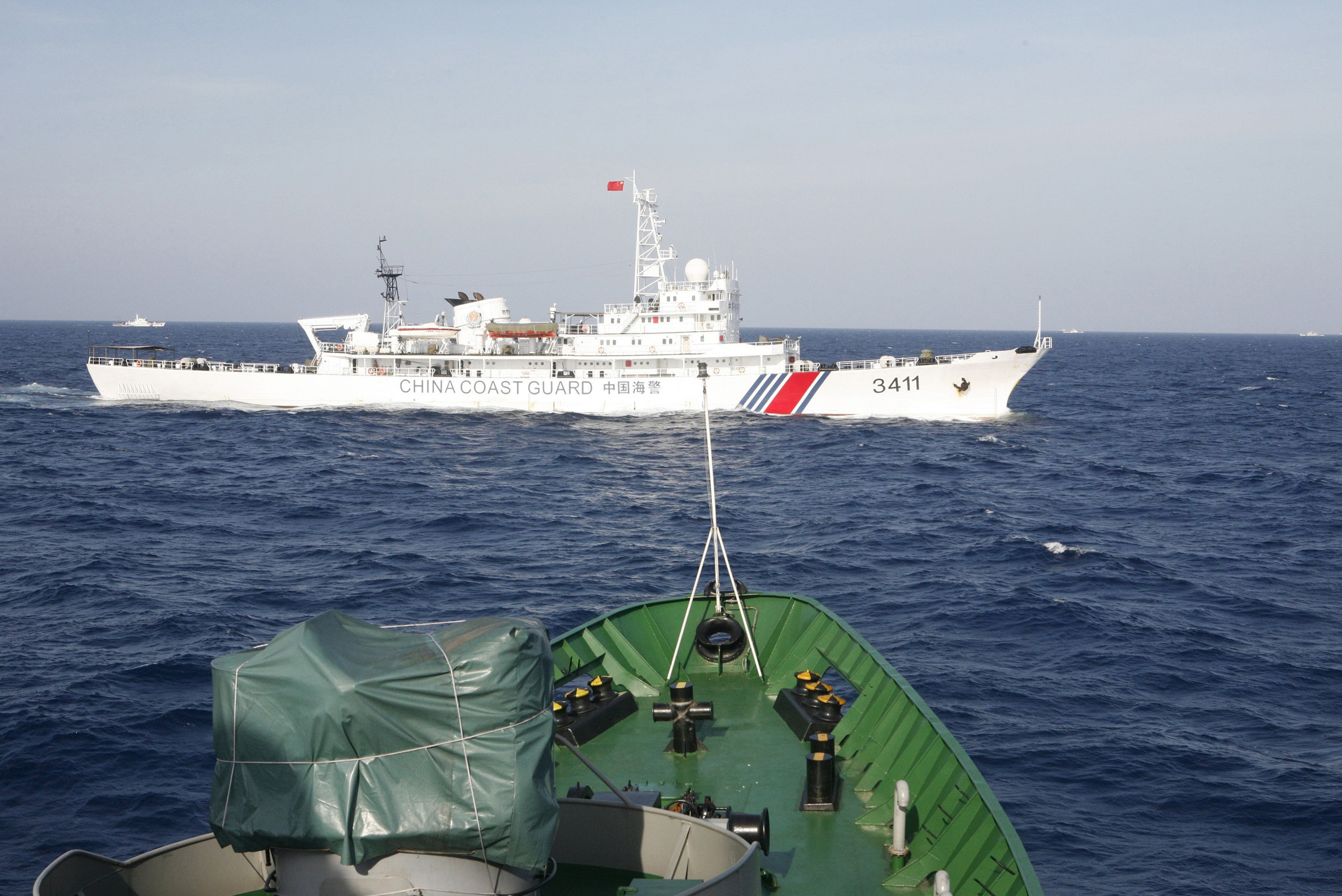 A ship (top) of Chinese Coast Guard is seen near a ship of Vietnam Marine Guard in the South China Sea, about 210 km (130 miles) off shore of Vietnam May 14, 2014. Vietnamese ships were followed by Chinese vessels as they neared China's oil rig in disputed waters in the South China Sea on Wednesday, Vietnam's Coast Guard said. Vietnam has condemned as illegal the operation of a Chinese deepwater drilling rig in what Vietnam says is its territorial water in the South China Sea and has told China's state-run oil company to remove it. China has said the rig was operating completely within its waters. REUTERS/Nguyen Minh (POLITICS MARITIME ENERGY) - RTR3P5C6
