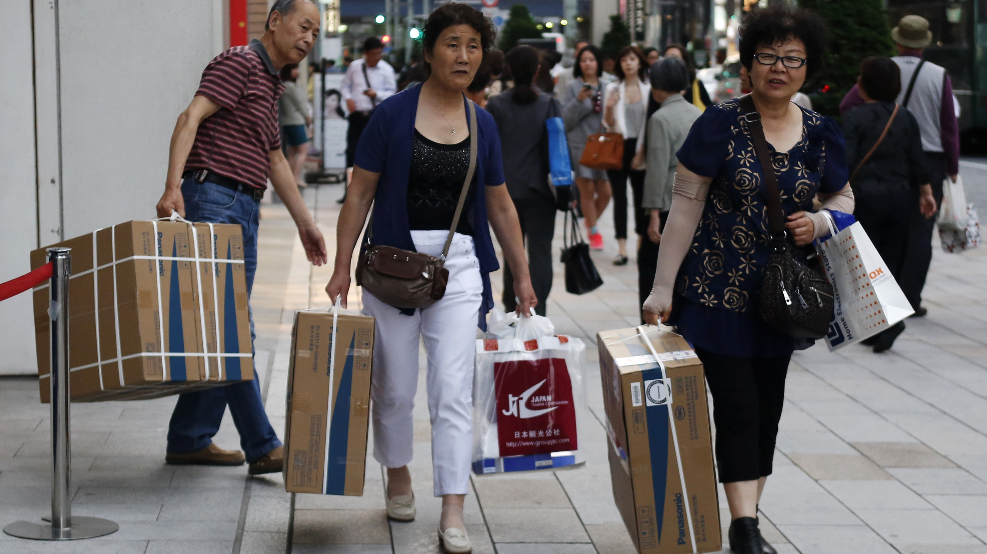 Chinese tourists carry packages of Panasonic Corp's washlet along Tokyo's Ginza Shopping district May 16, 2014. In ageing Japan, retailers are waking up to a hot new demographic: foreign visitors. Tourism contribution to the economy will take on increasing importance as Japan's population dwindles. Driven by government tourism promotions and lately a weaker yen, the number of inbound travellers has quietly doubled in the past decade to top 10 million for the first time last year. In 2013, they spent $14 billion on everything from powdered green tea to Prada handbags, to rare, red-coral rings. To match story JAPAN-RETAIL/TOURISM       Picture taken May 16, 2014. REUTERS/Yuya Shino (JAPAN - Tags: BUSINESS TRAVEL) - RTR3Q2SS