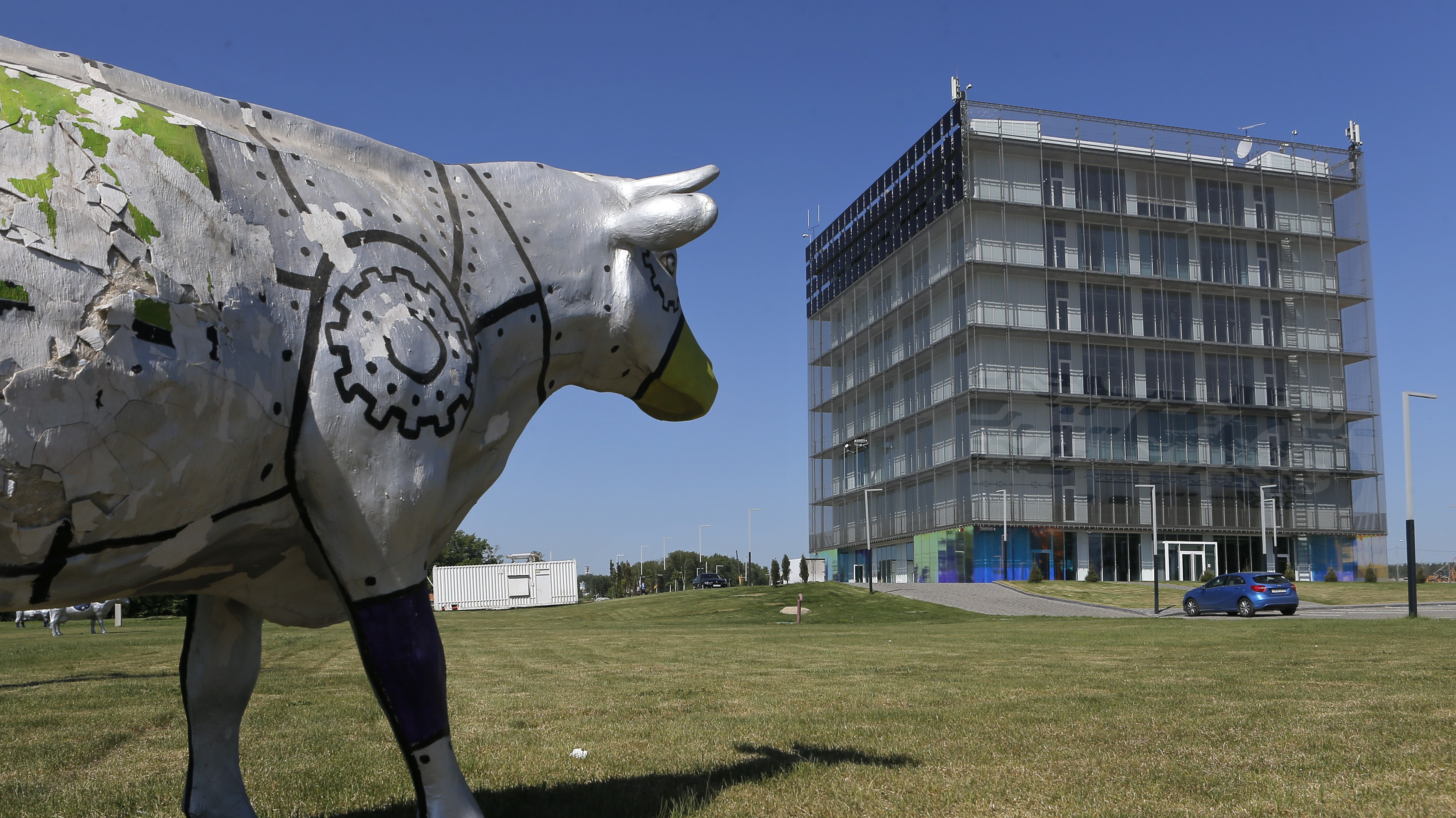 An exterior view shows the Skolkovo Hypercube at the Skolkovo Innovation Centre, with a sculpture of a cow seen in the foreground, on the outskirts of Moscow