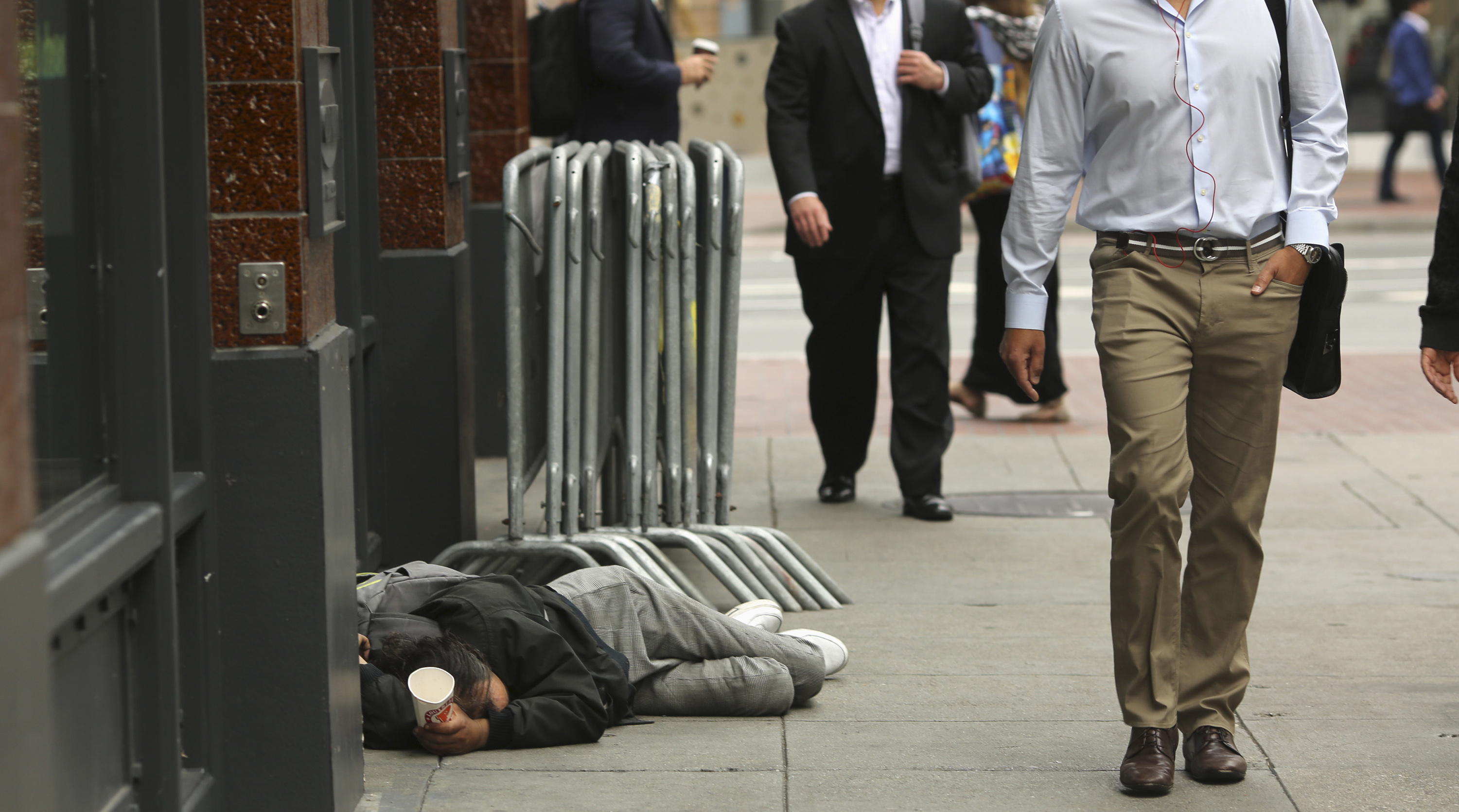Pedestrians pass a man laying on the sidewalk near the Powell Street BART and MUNI public transportation system station in San Francisco