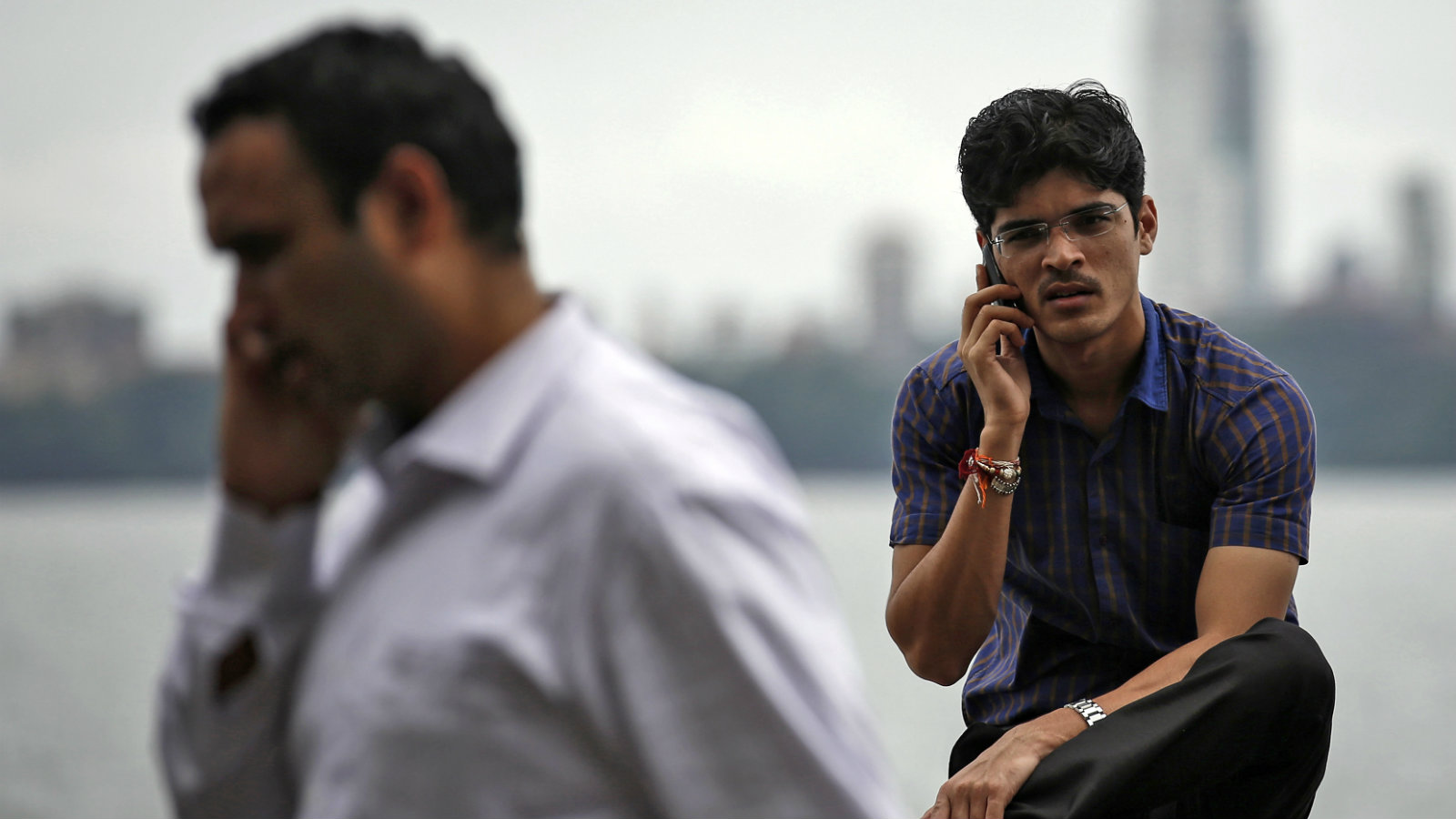 Men speak on their mobile phones on a seafront in Mumbai August 28, 2014. Google Inc's partnership with three Indian phone makers is set to rev up fast-growing demand for lower priced smartphones, and spell more trouble for Samsung Electronics which is rapidly losing share in emerging markets. Picture taken August 28.