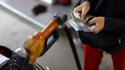 A worker at a state-owned Pertamina petrol station holds money as a motorcycle is filled with subsidised fuel in Jakarta, Indonesia.