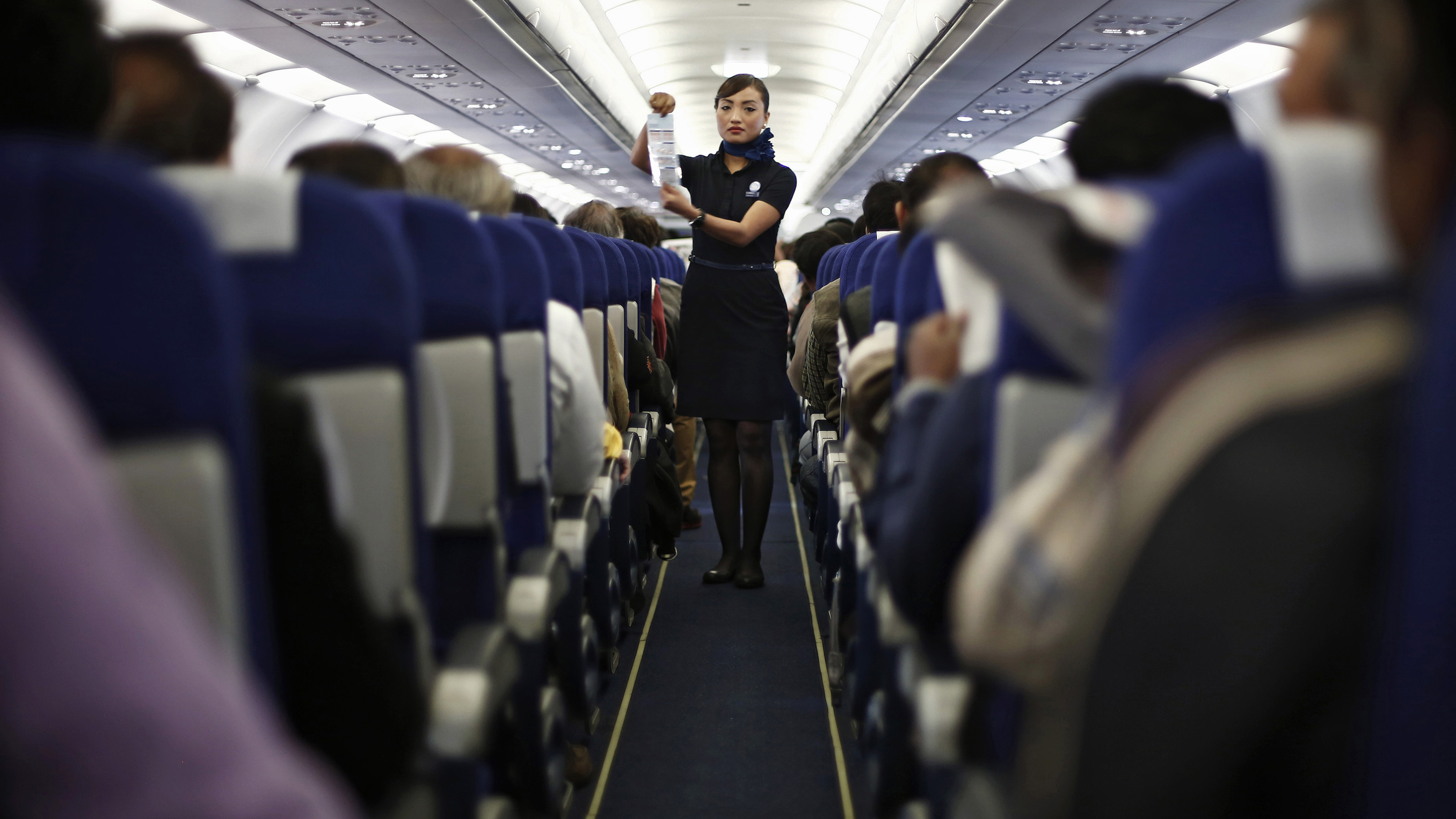 An Indigo Airlines' cabin crew member goes over safety guidelines during a flight