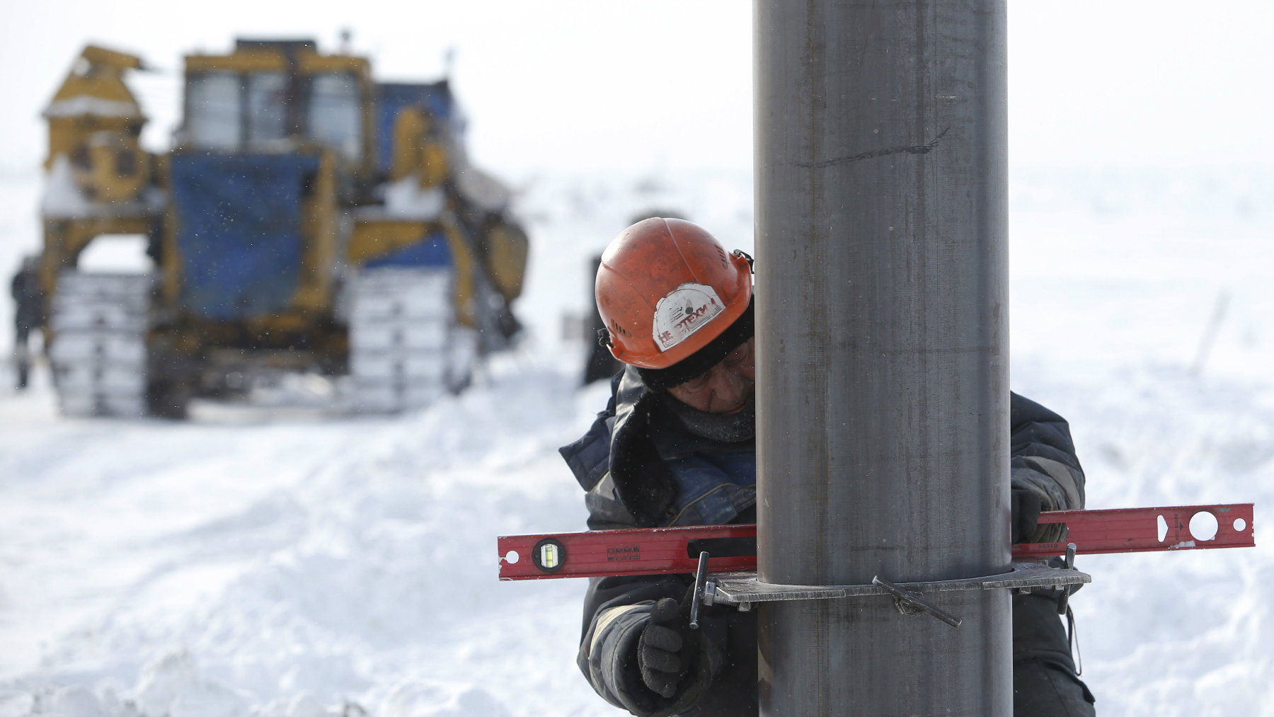 A worker installs a pipe support for the oil transportation to Vankor at the Rosneft company owned Suzunskoye oil field, north from the Russian Siberian city of Krasnoyarsk.