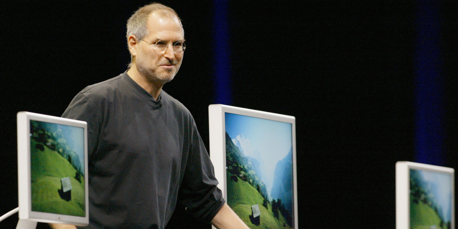 Apple Computer Inc. Chief Executive Steve Jobs stands with several Apple flat panel displays, as he previews the latest version of Apple's Mac OS X operating system called Tiger in San Francisco, California, June 28, 2004. Jobs also introduced a 30-inch flat panel display (C) in a sleeker and trimmer housing, its largest display yet, which adds to the 20-inch (L) and 23-inch displays (R) it already offers. REUTERS/Kimberly White  KW - RTR5EP7