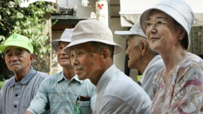 Japanese elderly people rest in the shade at a temple in Tokyo.