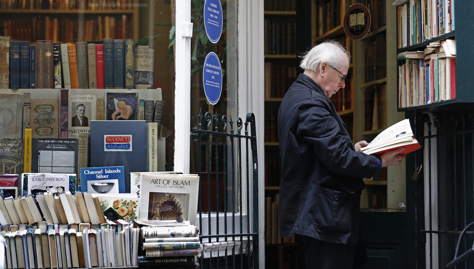 A man reads a book outside an antique bookshop in central London