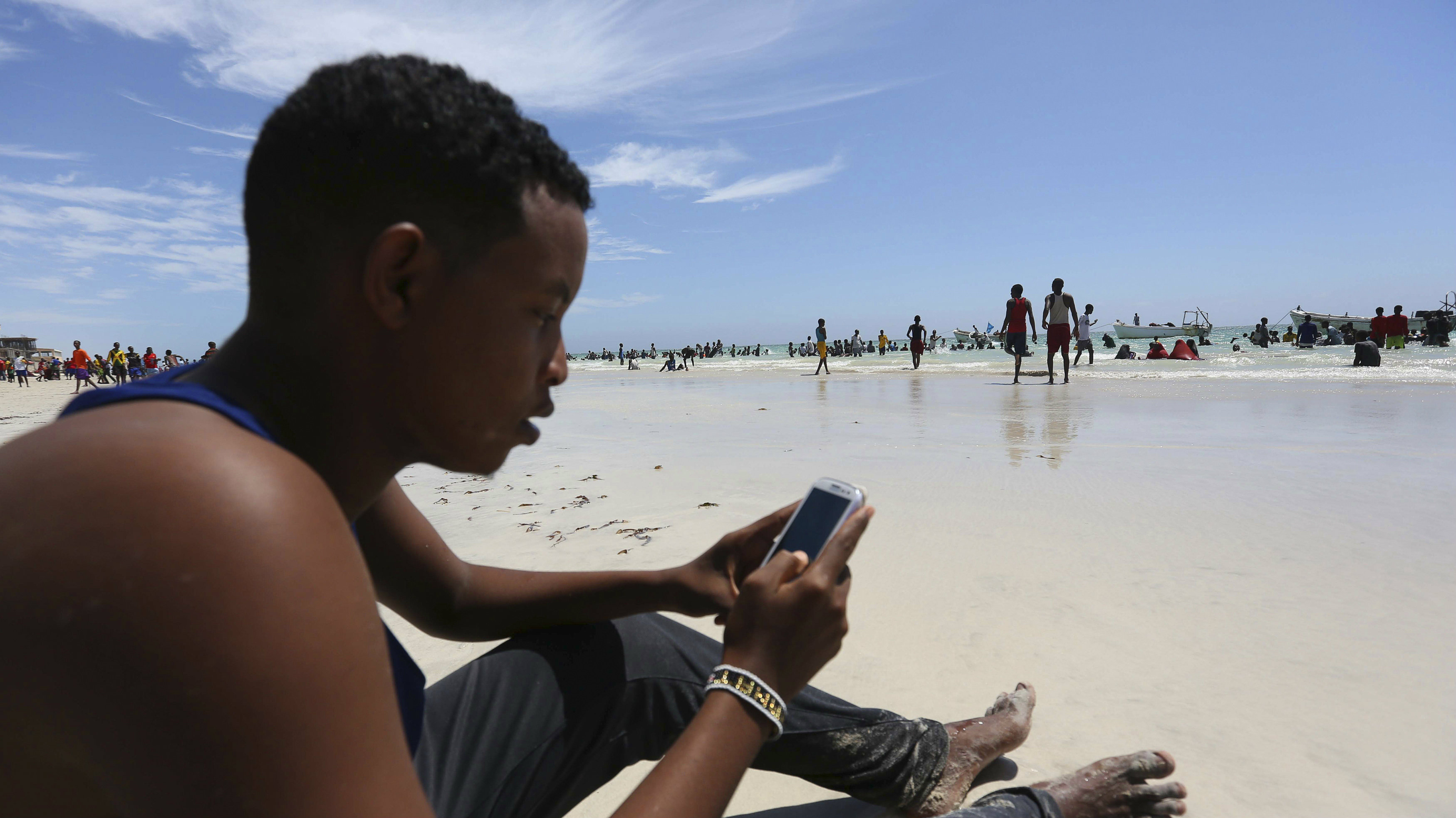 A Somali man browses the internet on his mobile phone at a beach along the Indian Ocean coastline in Somalia's capital Mogadishu, January 10, 2014.