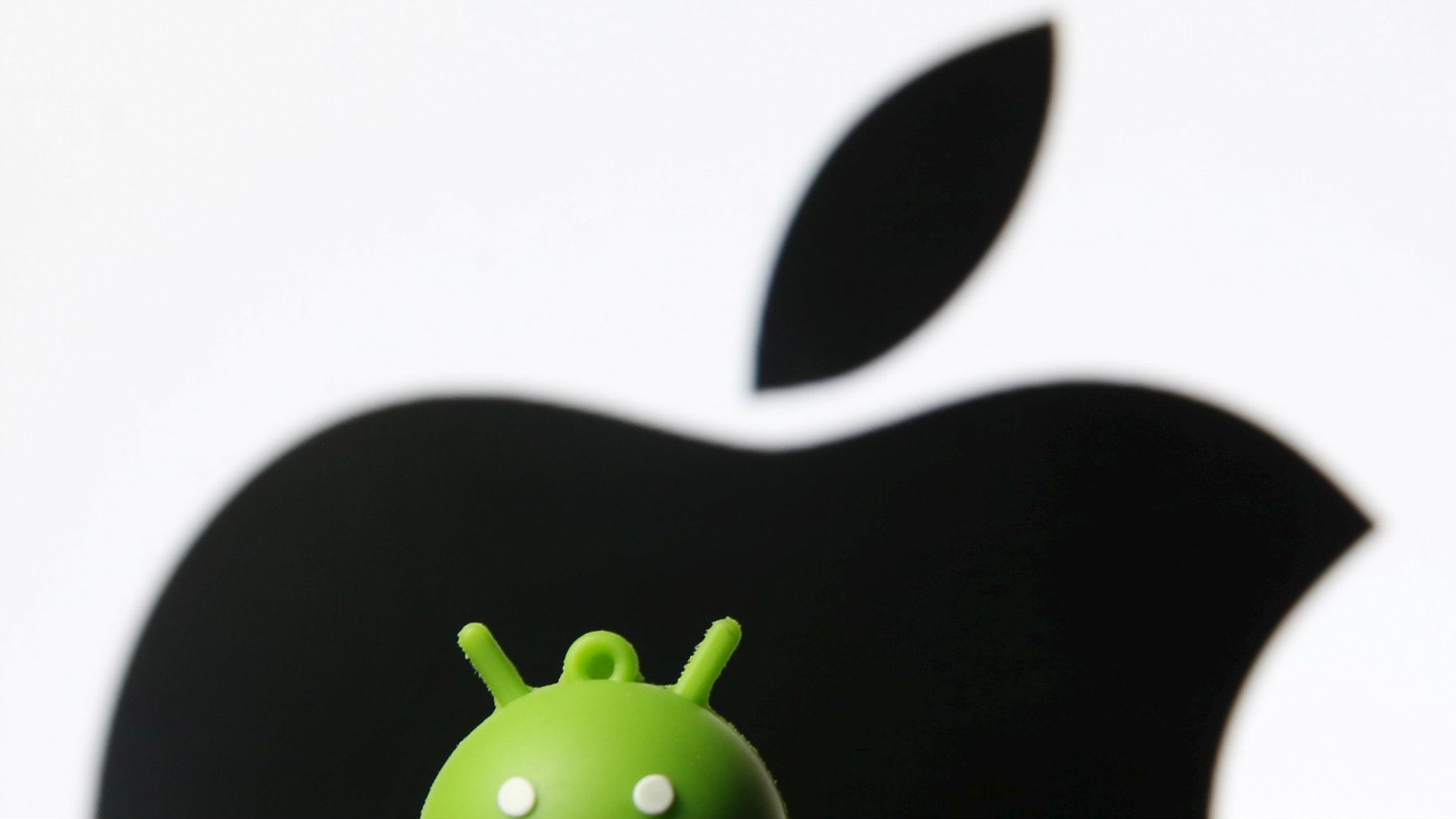 An Android mascot is seen in front of a displayed logo of Apple in this photo illustration taken in Zenica, Bosnia and Herzegovina.