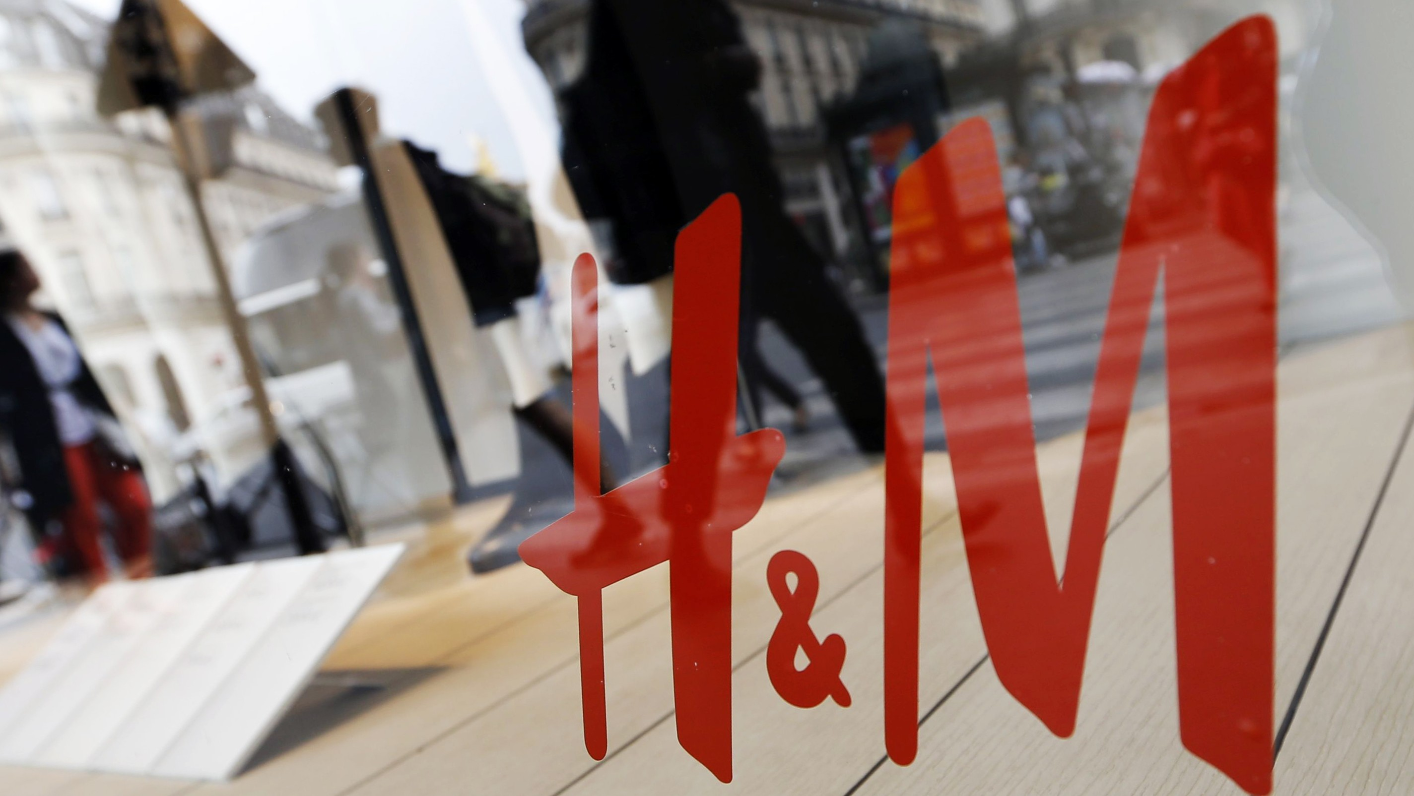 People walk past the window of a H&M store in Paris, France, August 24, 2015. Hennes & Mauritz, the world's second-biggest fashion retailer, is launching a new effort to promote recycling as it seeks to cut its environmental impact, boost its ethical credentials and address looming shortages of raw materials.    REUTERS/Regis Duvignau - RTX1QJQX