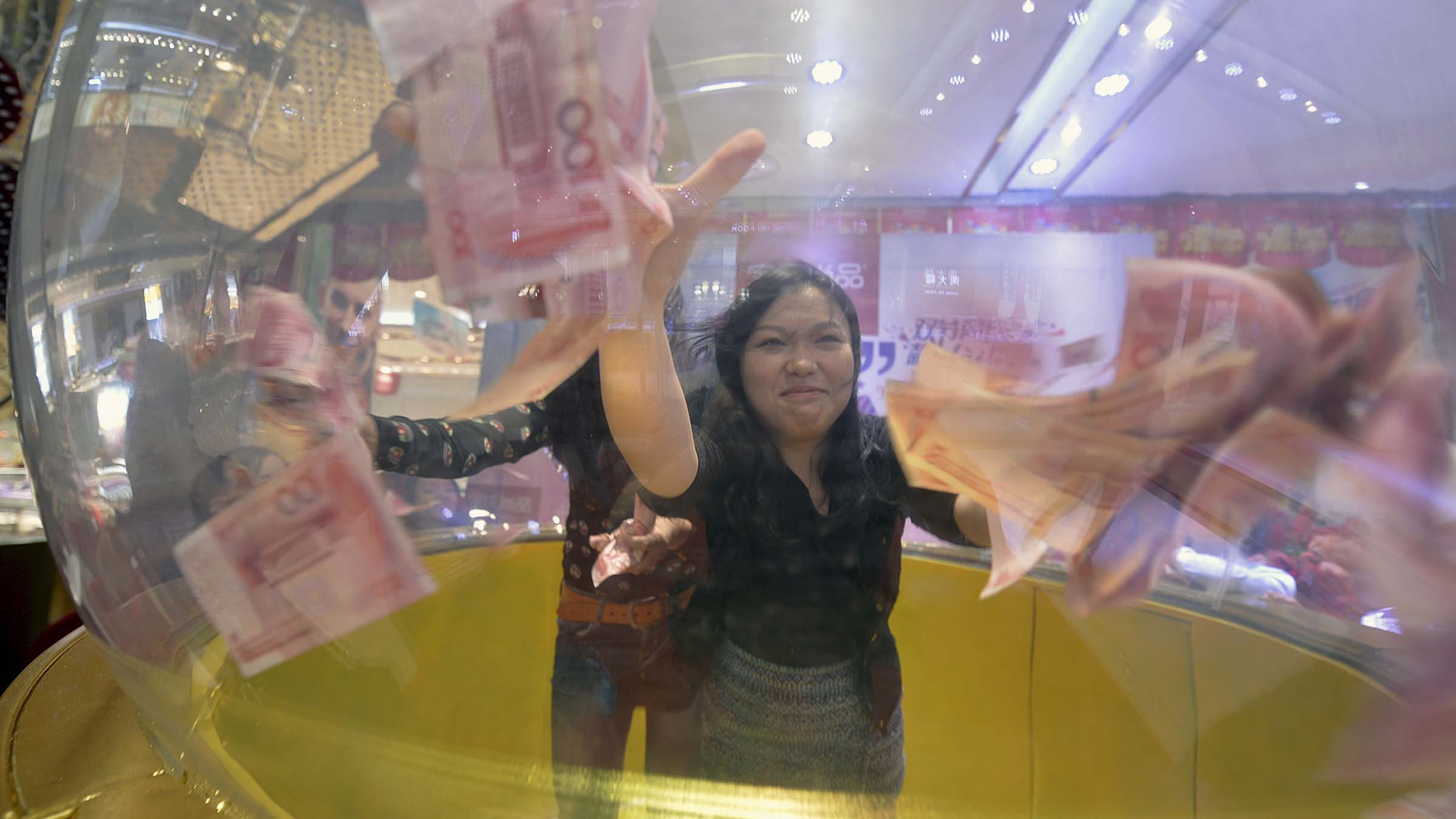 Participants try to catch 100 yuan banknotes flying inside a dome during a promotional event of a jewelry store in Nanjing