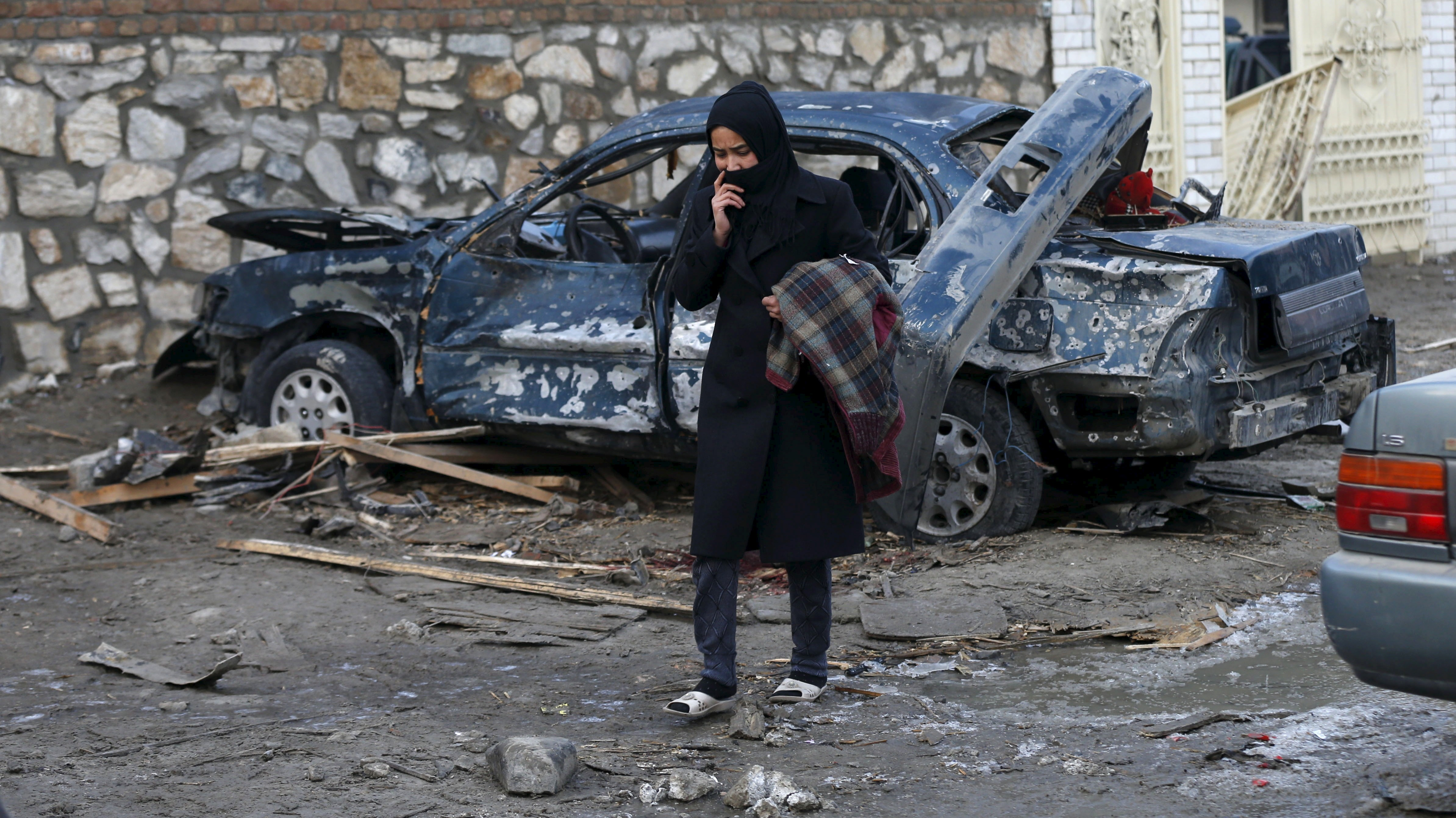"""An Afghan woman walks past a damaged car after a suicide attack on French restaurant  """"Le Jardin""""  in Kabul, Afghanistan January 2, 2016. The attack on Friday killed a 12-year-old boy and wounded more than a dozen other people, officials said."""