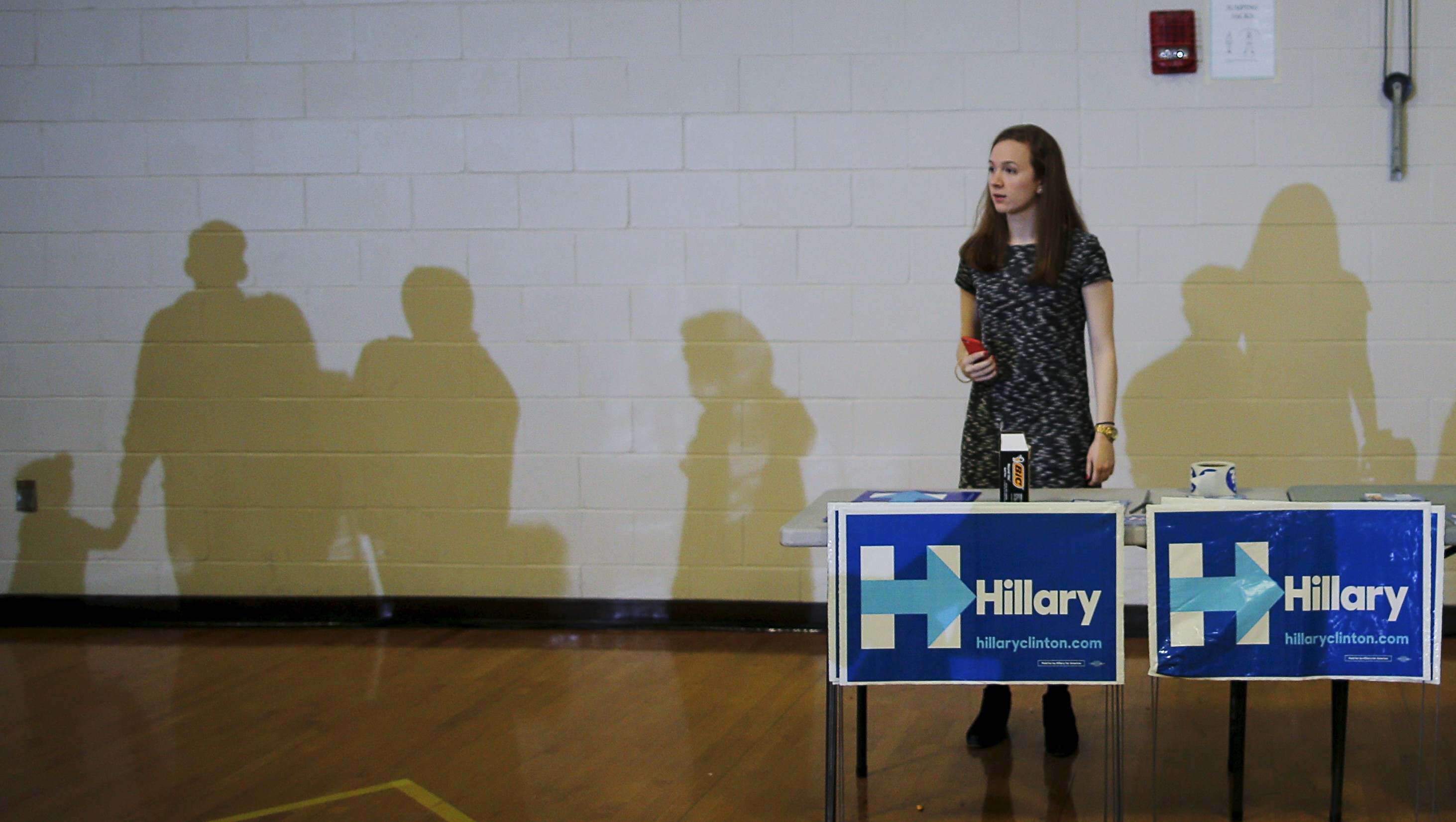 Campaign volunteer Katie Stallman waits to hand out signs before a town hall meeting with U.S. Democratic presidential candidate Hillary Clinton in Derry