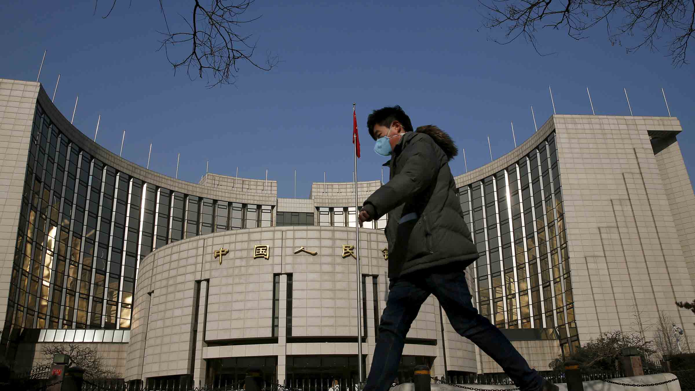 A man walks past the headquarters of the People's Bank of China, the country's central bank, in Beijing