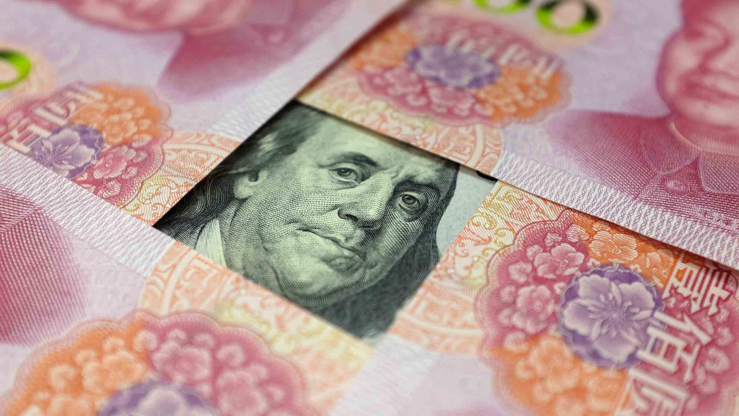 A U.S. 100-dollar banknote with a portrait of Benjamin Franklin and Chinese 100-yuan banknotes with portrait of late Chinese Chairman Mao Zedong are seen in the picture illustration in Beijing
