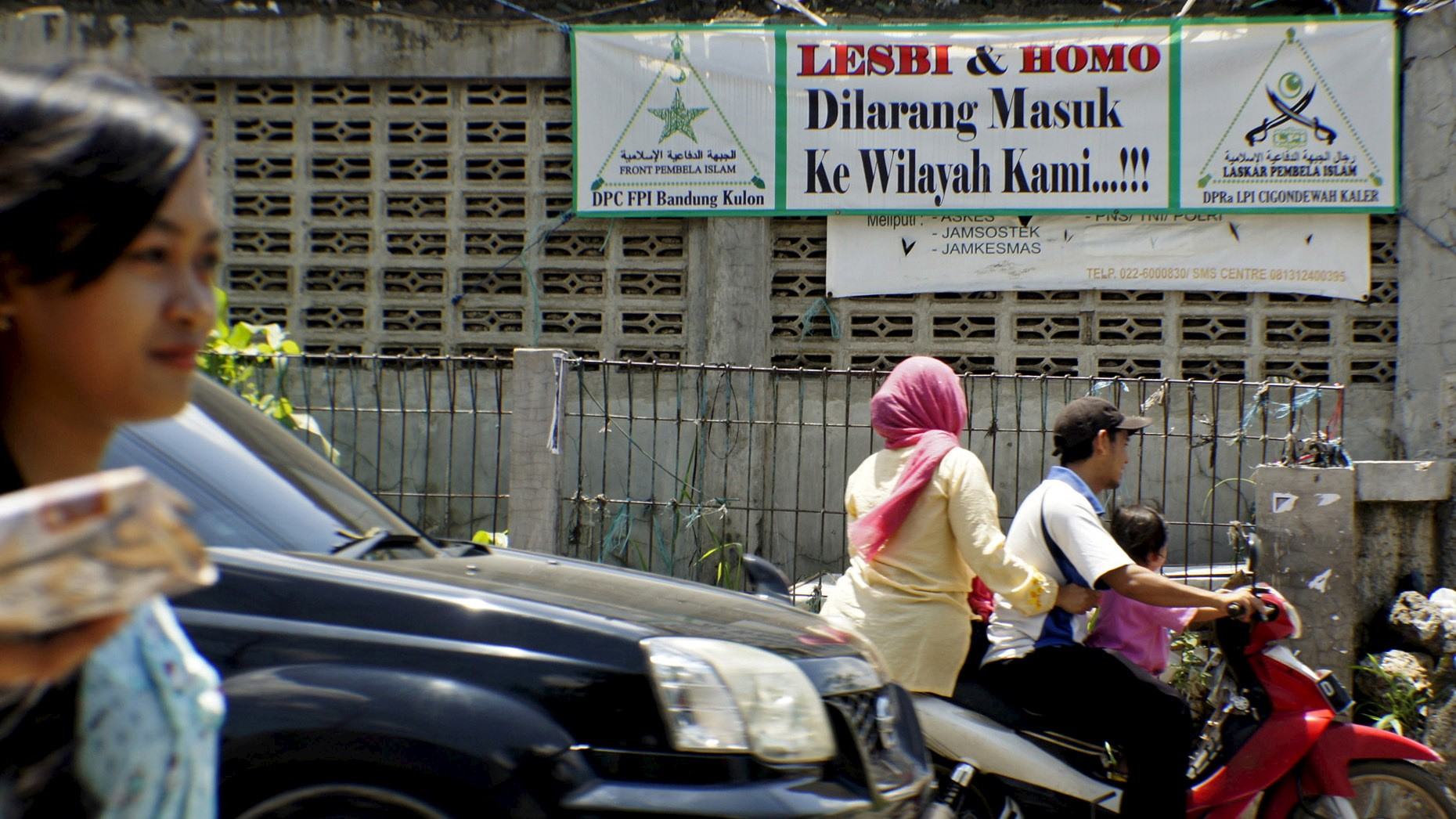 People drive a motorcycle past a banner put up by the hardline Islamic Defenders Front calling for gay people to leave the Cigondewah Kaler area in Bandung